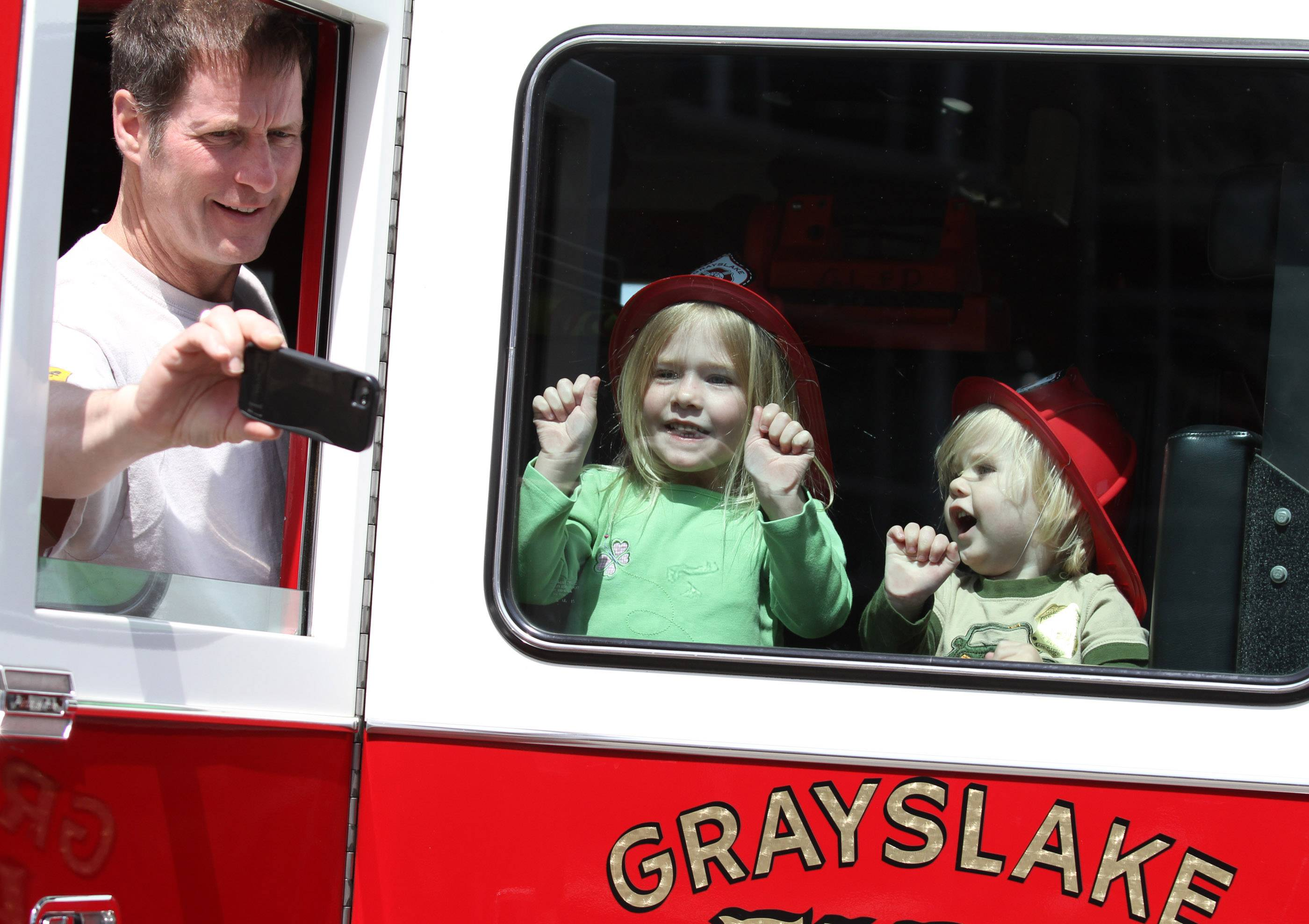 Mark Pratt takes a selfie with his daughter Katie, 4, and son William, 1, in a Grayslake fire truck at Northwestern Grayslake's annual Children's Health and Safety Fair at Northwestern Grayslake Outpatient Center on Saturday in Grayslake.