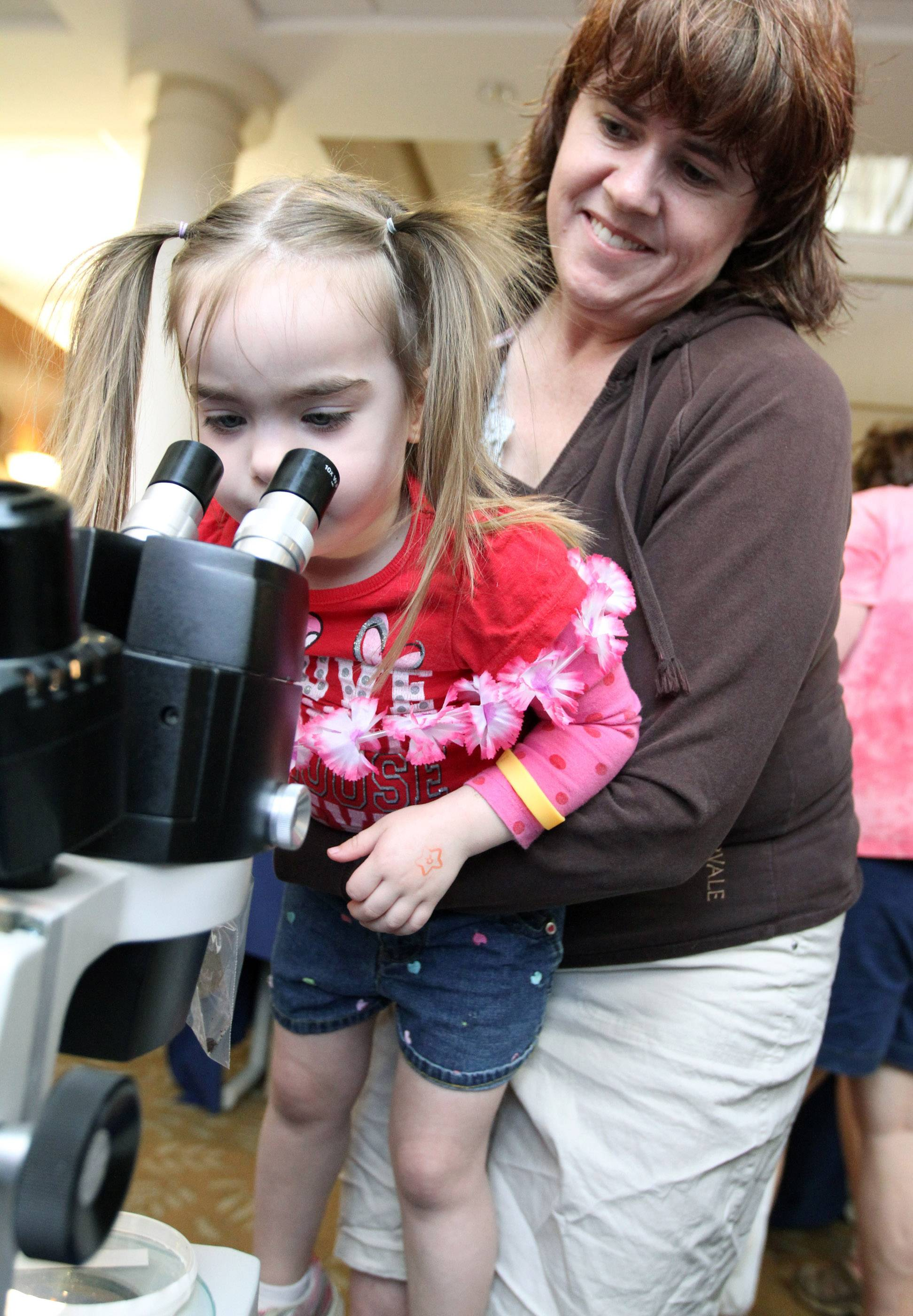 JoAnn Stewart holds her daughter, Claire, 3, of to a telescope to view germs at Northwestern Grayslake's annual Children's Health and Safety Fair at Northwestern Grayslake Outpatient Center on Saturday in Grayslake.