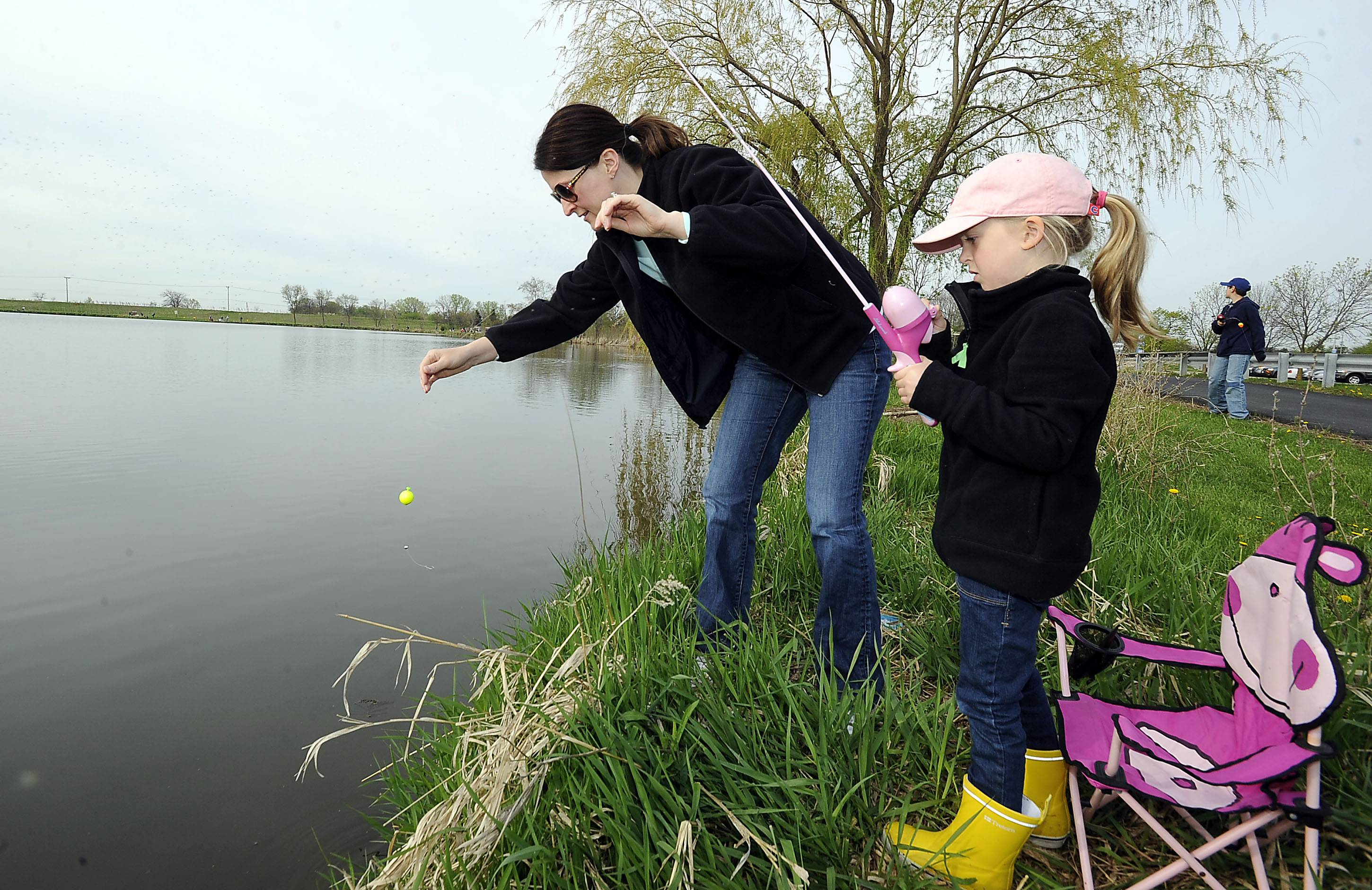 Jen Bubanovich of Palatine helps her daughter Emma, 5, with her fishing gear at the Palatine Park District Fishing Derby. They managed to catch one small bluegill fish in the early morning family outing.