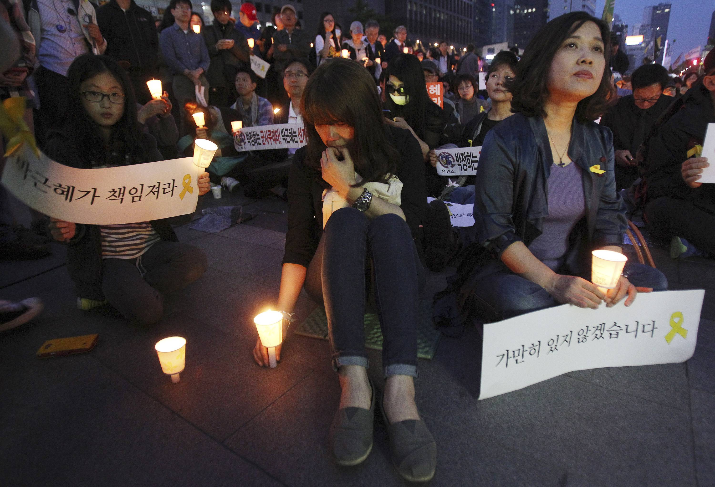 "A woman places a candle during a rally to pay tribute to the victims and missing passengers of the sunken ferry Sewol in Seoul, South Korea, Saturday, May 10. Bad weather and the deterioration of internal partitions in the sunken ferry are hampering the search for those still missing in the disaster, South Korean officials said Saturday. The placards read: ""Your fault, President."""