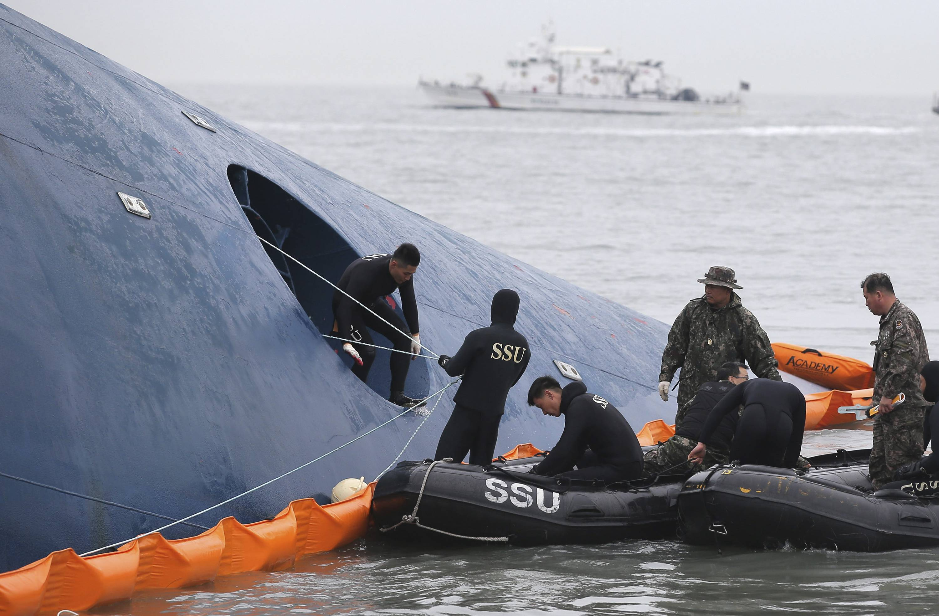 In this April 17 photo, South Korean rescue team members try to rescue passengers trapped in the ferry Sewol sinking in the water off South Korea's southern coast near Jindo. Internal partitions in the ferry have become waterlogged and started to bend, said government task force spokesman Ko Myung-seok. Coast guard officials said this can prevent divers from entering different parts of the ferry. Ko also said divers were unable to carry out underwater searches Saturday because of bad weather.