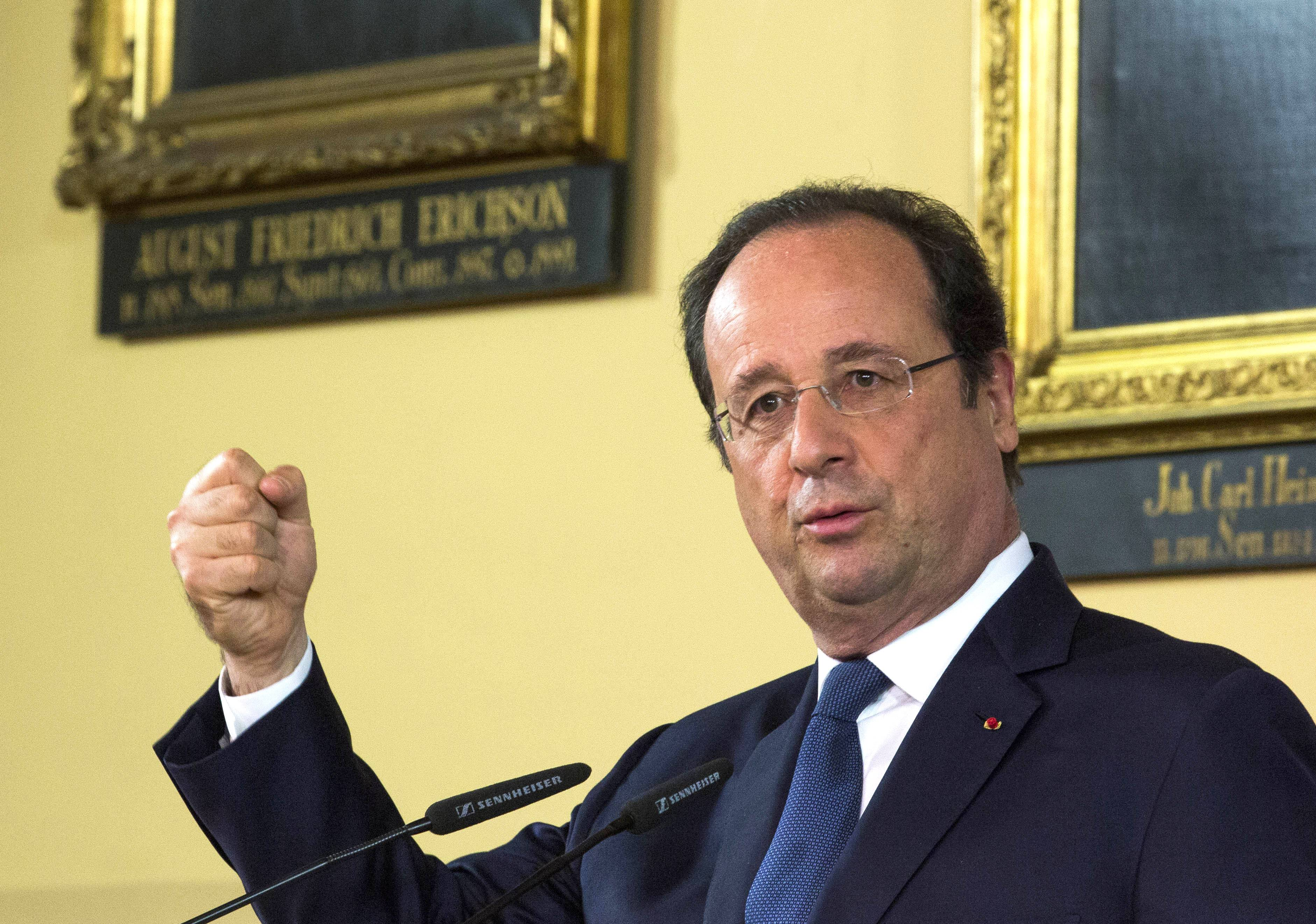 French President Francois Hollande gestures during a news conference with German Chancellor Merkel at the town hall in Stralsund, northern Germany, Saturday, May 10, during the second day of Hollande's two days visit to Merkel's scenic home constituency on the Baltic coast. One of the main talking points is expected to be over whether the European Union should impose further sanctions on Russia, for its involvement in the Ukraine crisis.