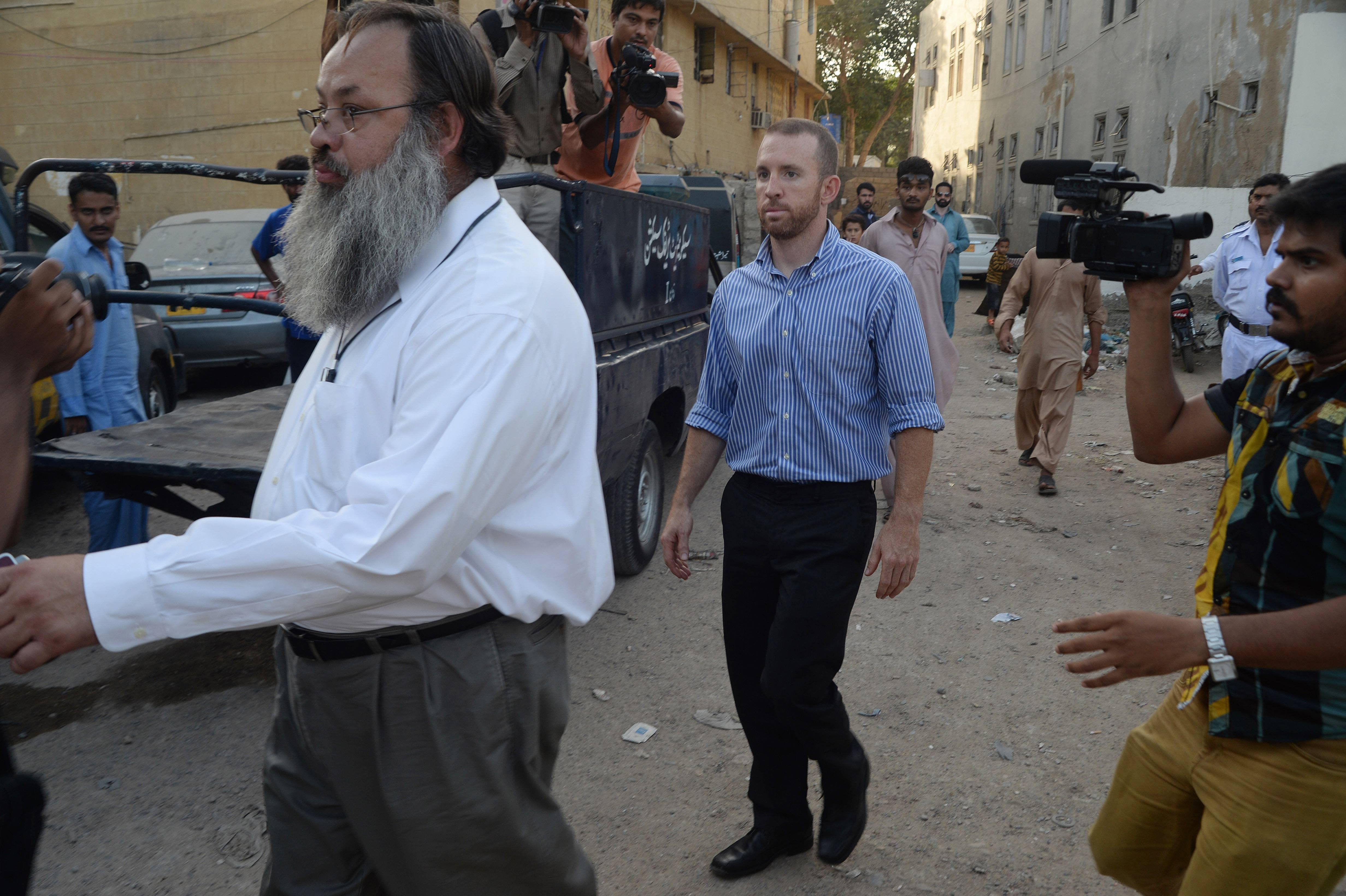 An American national, center, reportedly working for the FBI, leaves a police station in Karachi, Pakistan, Thursday, May 8. Pakistan released an FBI agent on bail Thursday after three days in custody, officials said, a move that is likely to prevent the situation from escalating into a diplomatic spat. The American man was detained after airport authorities found him carrying ammunition and three knives Monday as he was about to board a flight for the Pakistani capital, Islamabad.