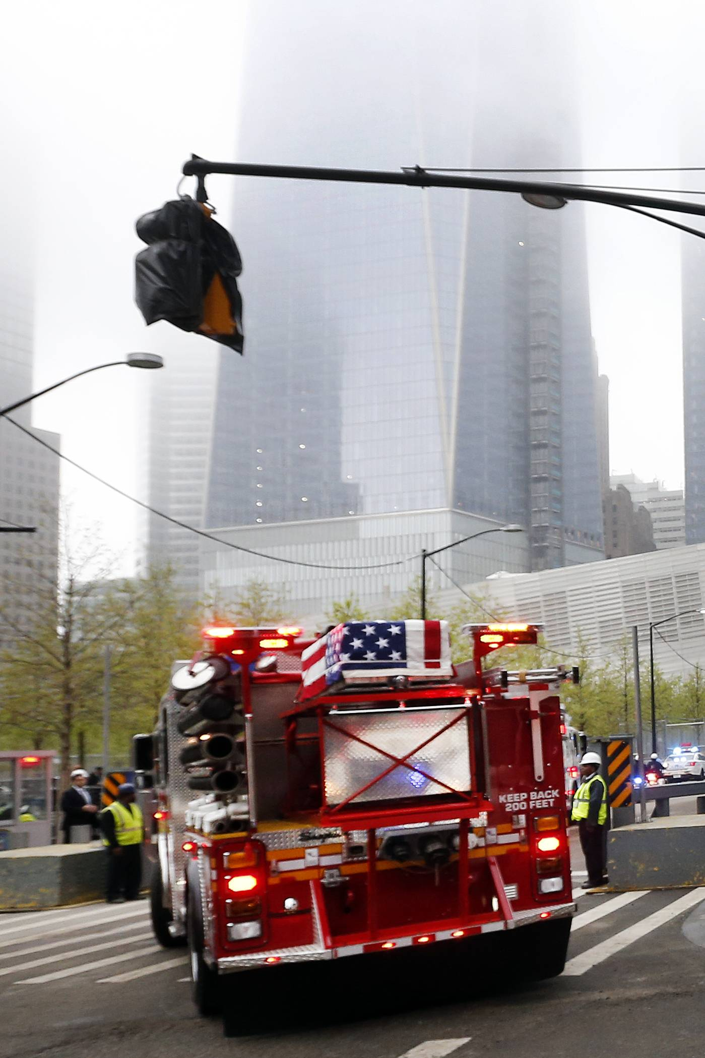 A flag-draped casket can seen atop a fire truck as the motorcade arrives for the ceremonial transfer of unidentified remains of those killed at the World Trade Center from the Office of the Chief Medical Examiner to the World Trade Center site, Saturday, May 10, in New York. The remains will be transferred to an underground repository in the same building as the National September 11 Memorial Museum.