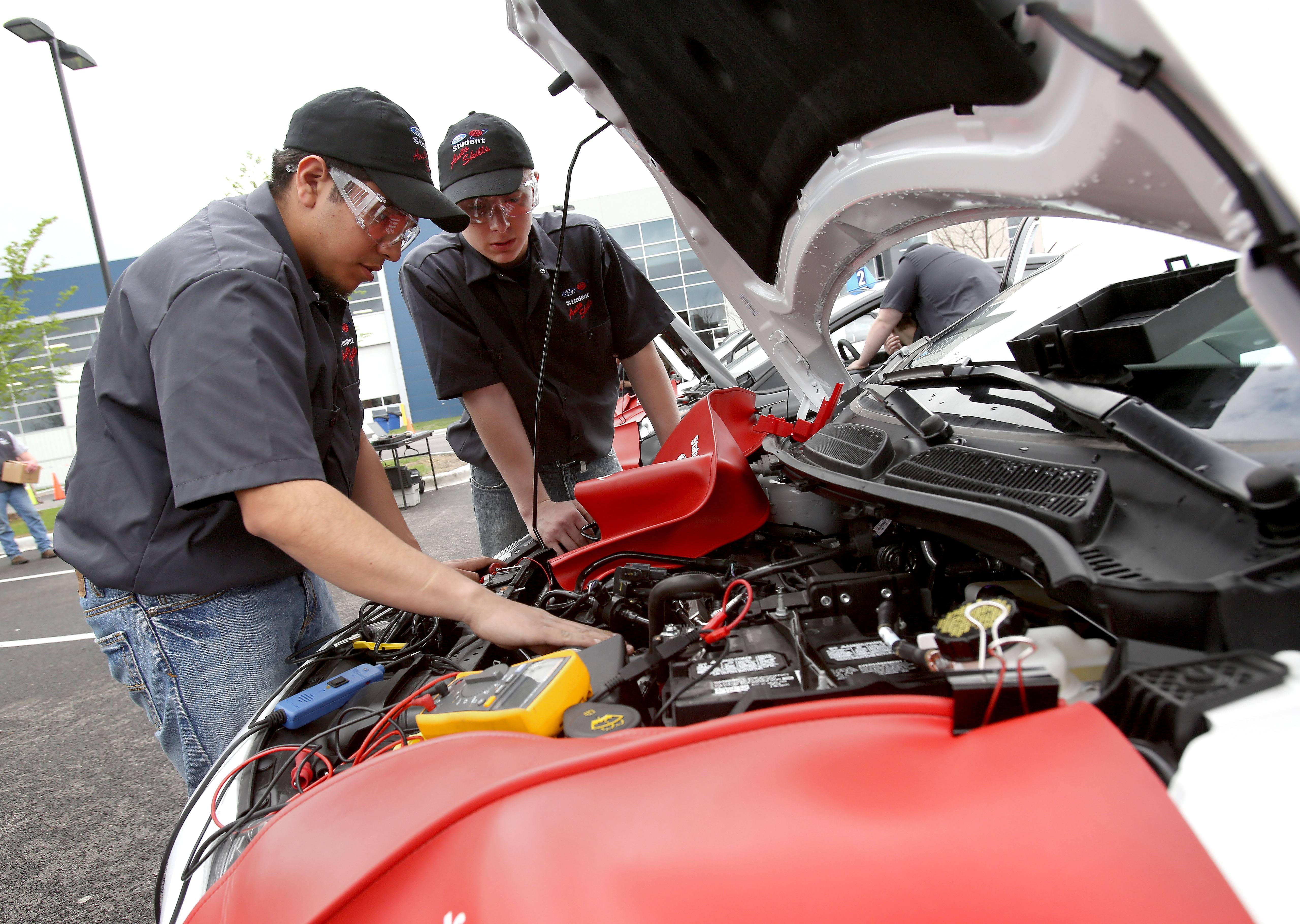 "Bev Horne/bhorne@dailyherald.comSamuel Ramos, left, and Ryan Szabelski from Addison Trail High School work to find ""bugs"" that were intentionally installed in a 2014 Ford Fiesta during the Ford/AAA Student Auto Skills competition at Universal Technical Institute in Lisle."