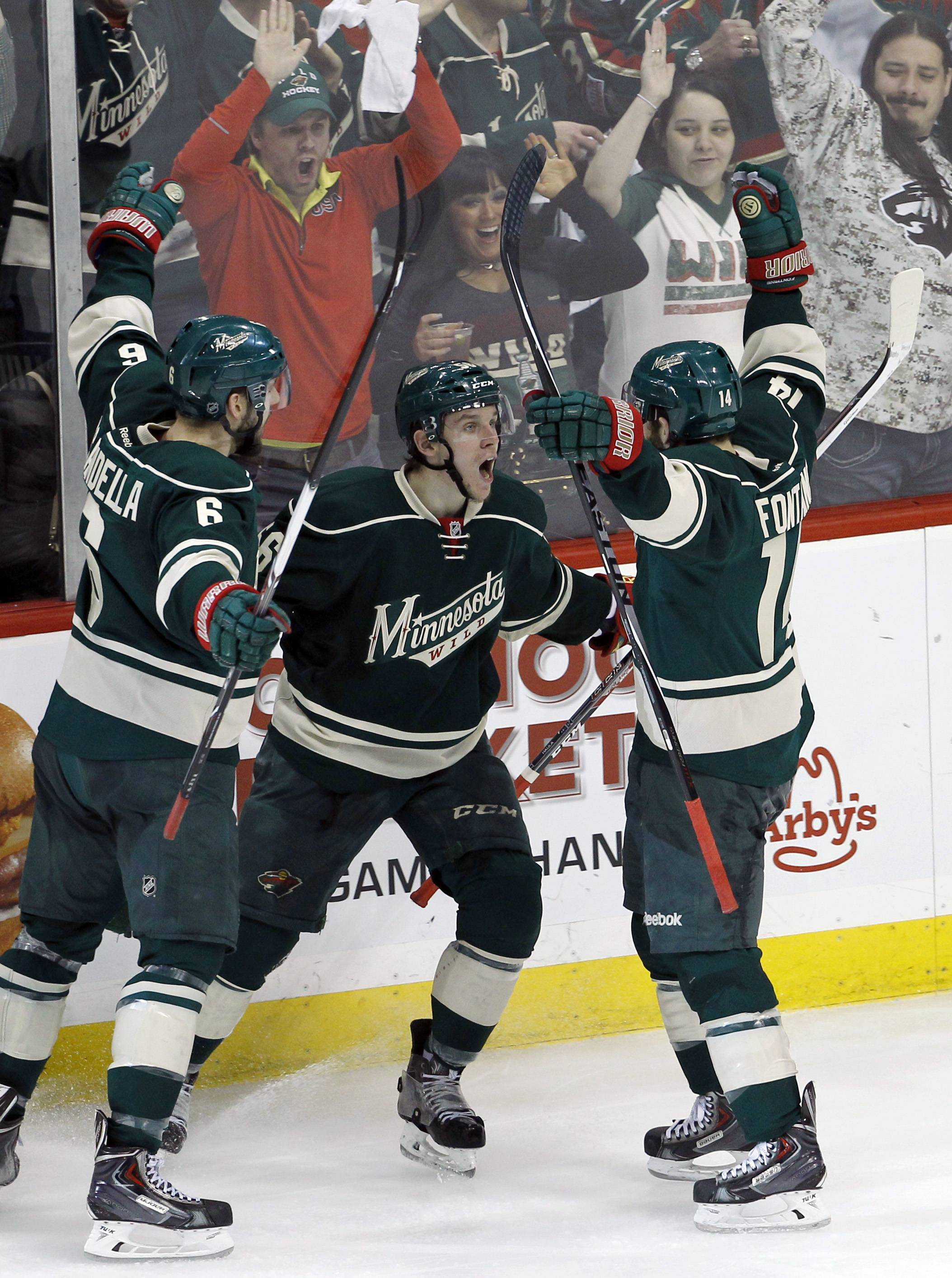 Minnesota Wild left wing Erik Haula, center, of Finland, celebrates with teammates Marco Scandella (6) and Justin Fontaine, right, after scoring on Chicago Blackhawks goalie Corey Crawford during the third period of Game 3 of an NHL hockey second-round playoff series Tuesday in St. Paul, Minn. The Wild won 4-0.