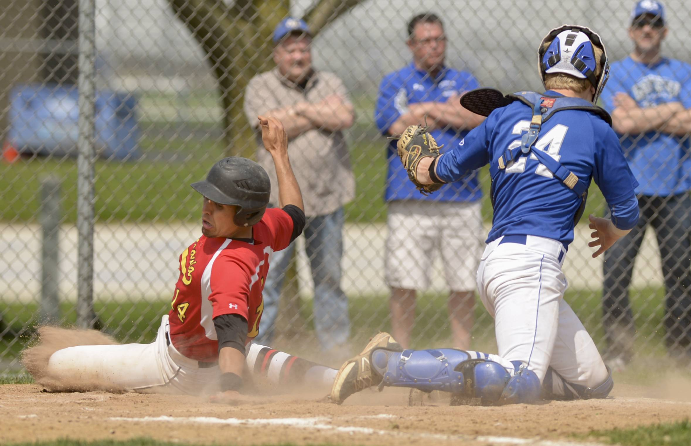 Batavia's Micah Coffey slides safely into home past Geneva's Nate Montgomery to score the second of his team's five runs in the third inning in Geneva Saturday.