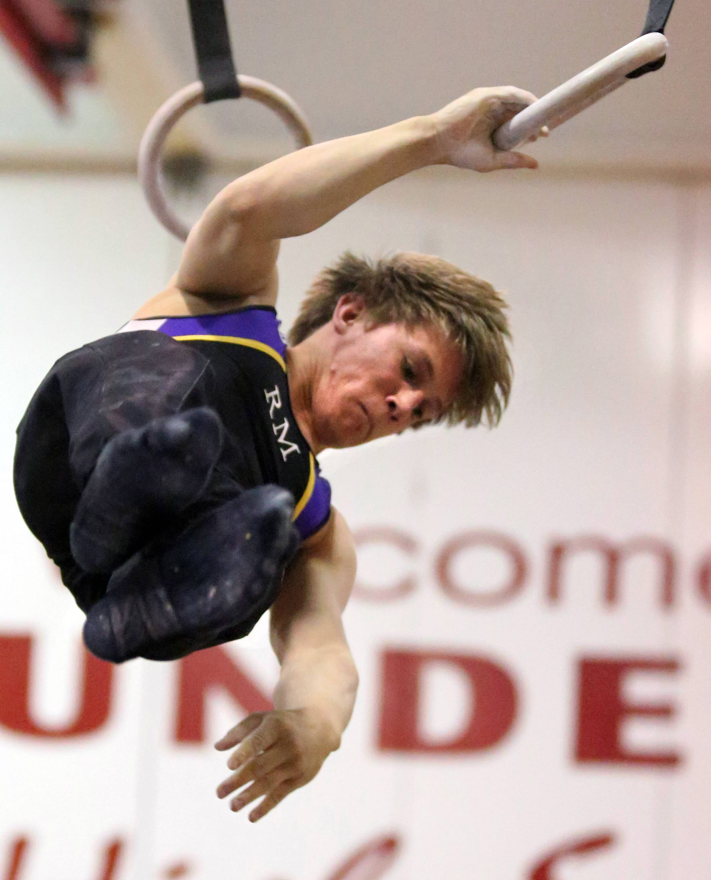Rolling Meadows' Alex Smith dismounts from the still rings at the Mundelein boys gymnastics sectional on Saturday.
