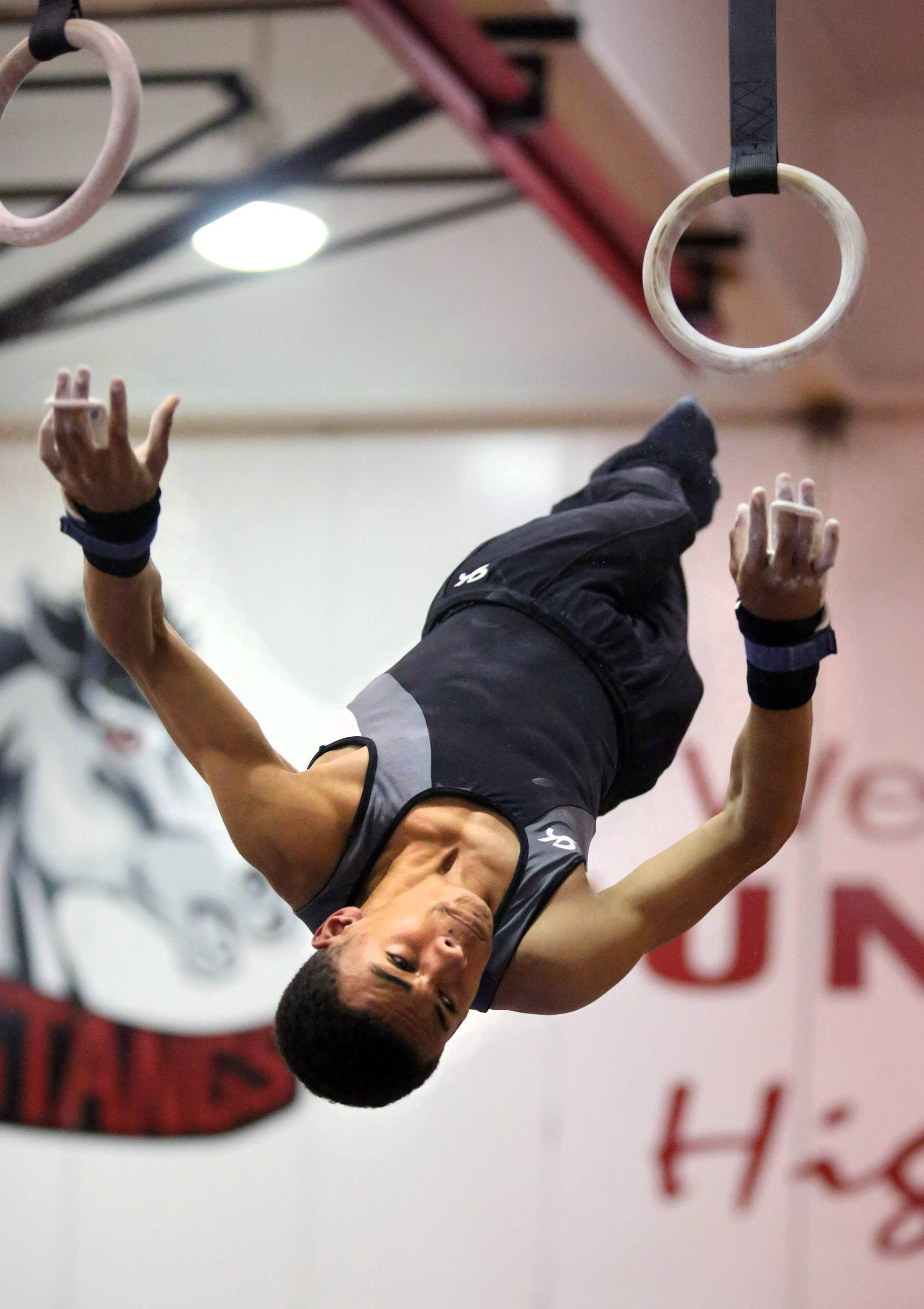 Elgin's Steve Merena dismounts from the still rings at the Mundelein boys gymnastics sectional on Saturday.