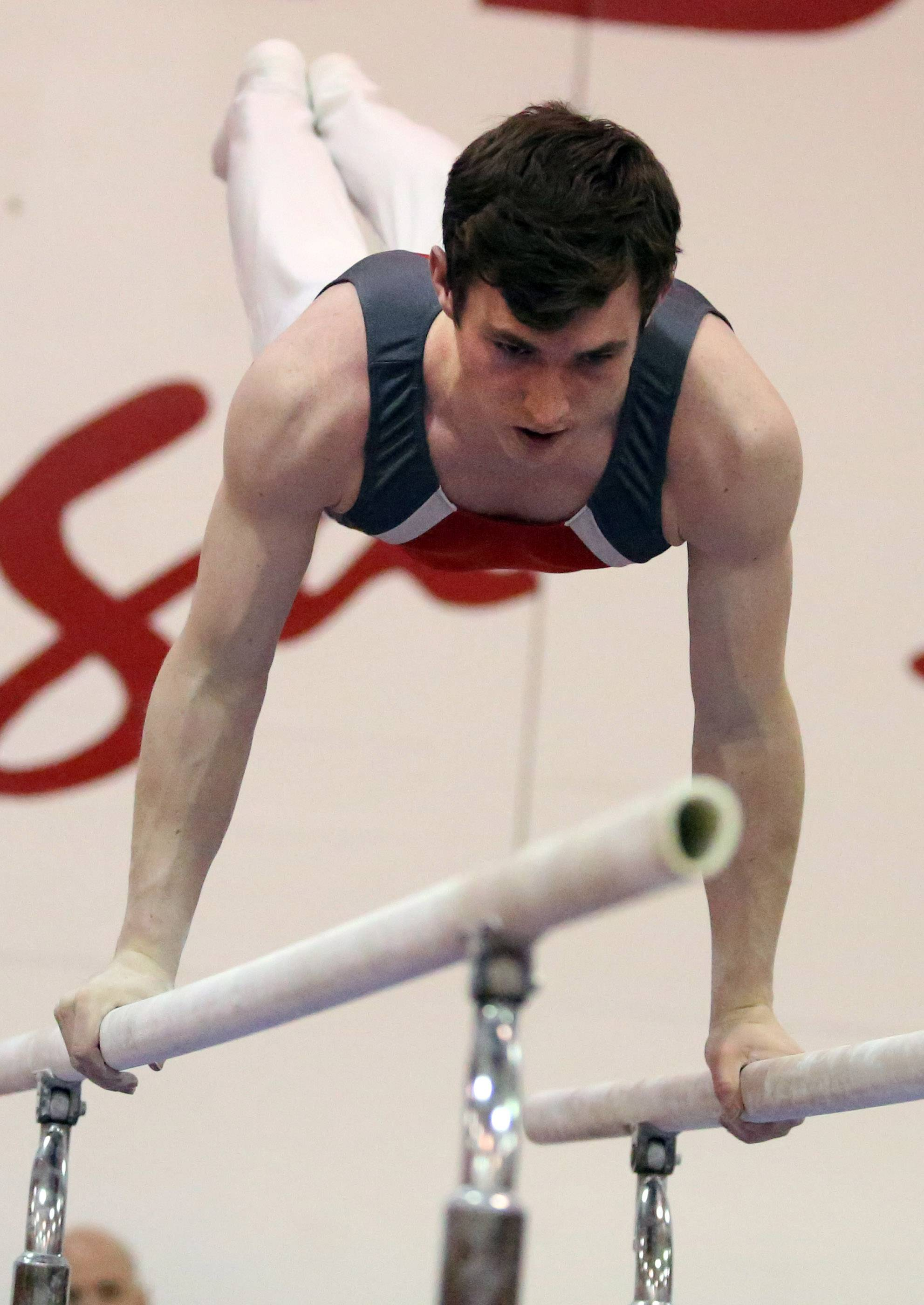 Mundelein's Cameron Mueller on the parallel bars at the Mundelein boys gymnastics sectional on Saturday.
