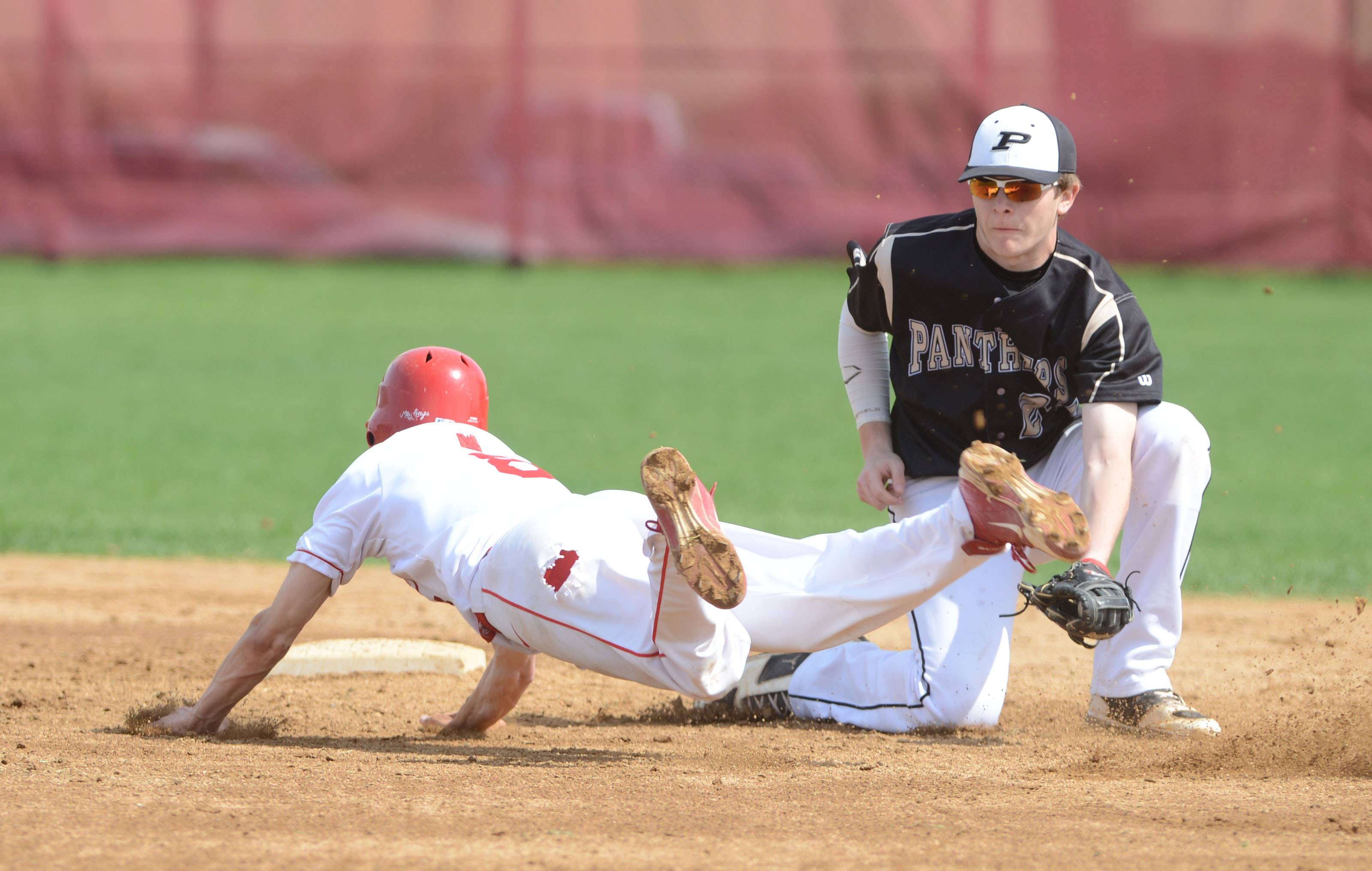 #8 Jason Wegner of Naperville Central dives into second while #24 Sam Ledbetter of Glnebard north puts the tag on him during the Glenbard North at Naperville Central baseball game Saturday. He was safe.