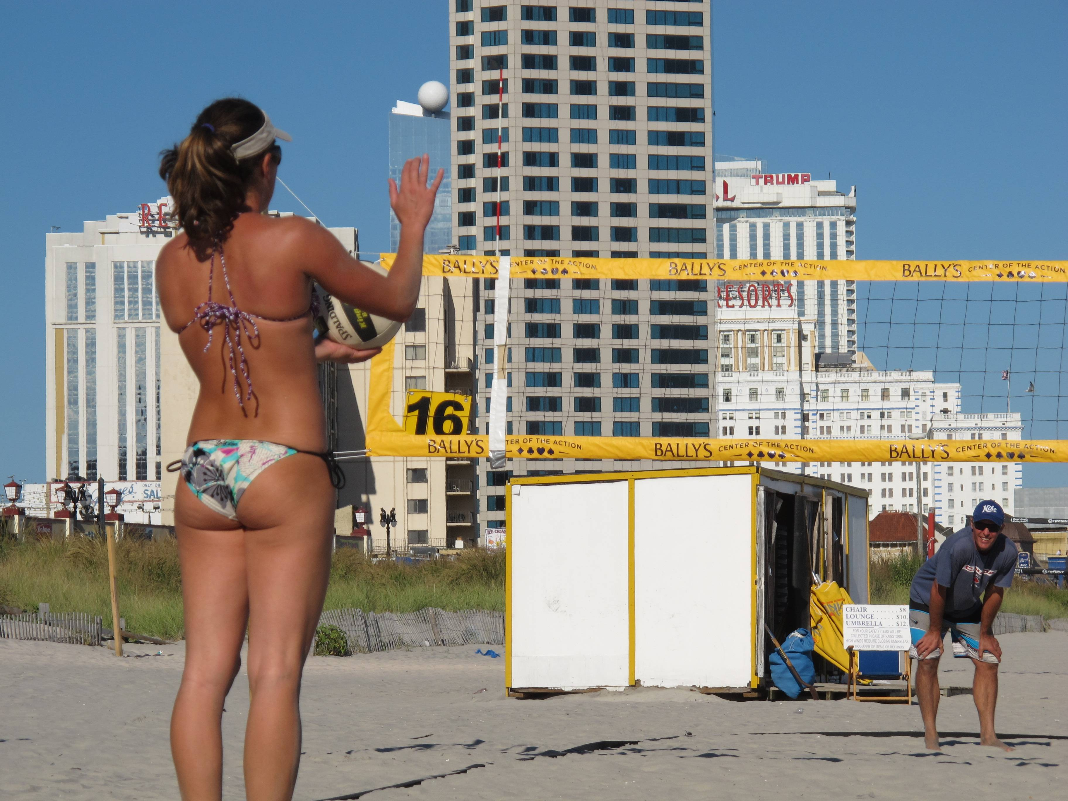 In this Sept. 6, 2013 photo, a woman prepares to serve a volleyball during a game on the Atlantic City N.J. beachfront before a national pro volleyball tour began there. That tour will return again this summer, along with many other free activities that don't involve gambling. (AP Photo/Wayne Parry)
