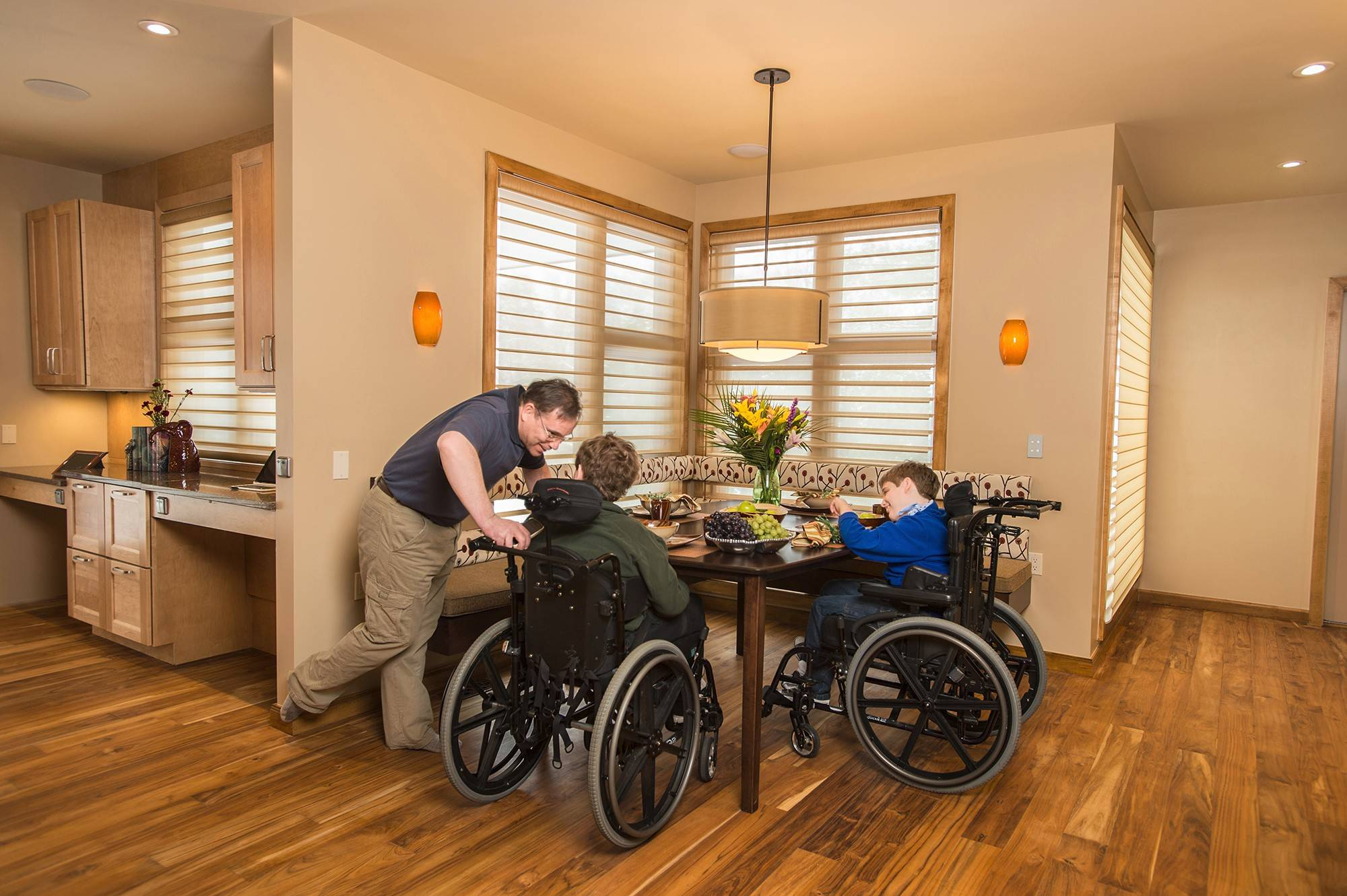 Andy Cibula talks with sons Joshua and David at the dining table in their custom-designed home. The table was custom built because wheelchair arms scraped along the original's underside. A banquette was chosen for seating instead of chairs, which could be obstructions.