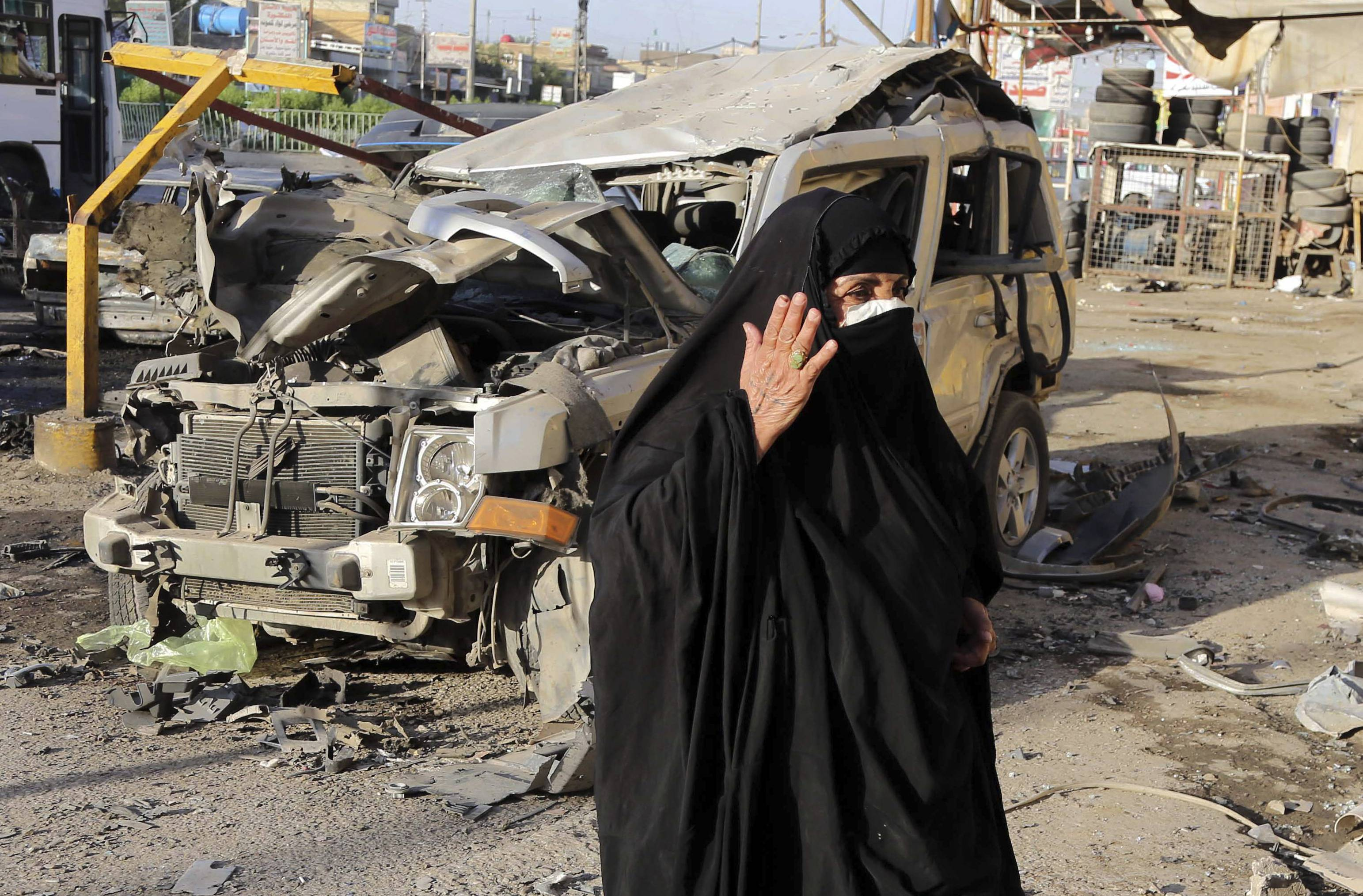A woman looks at damage from a Saturday car bomb attack in the mainly Shiite Habibiya neighborhood of Baghdad, Iraq, Sunday. A series of bombings on Saturday in Iraq killed and wounded scores of people, a day after army shelling killed many civilians and gunmen in the militant-held city of Fallujah, authorities said.