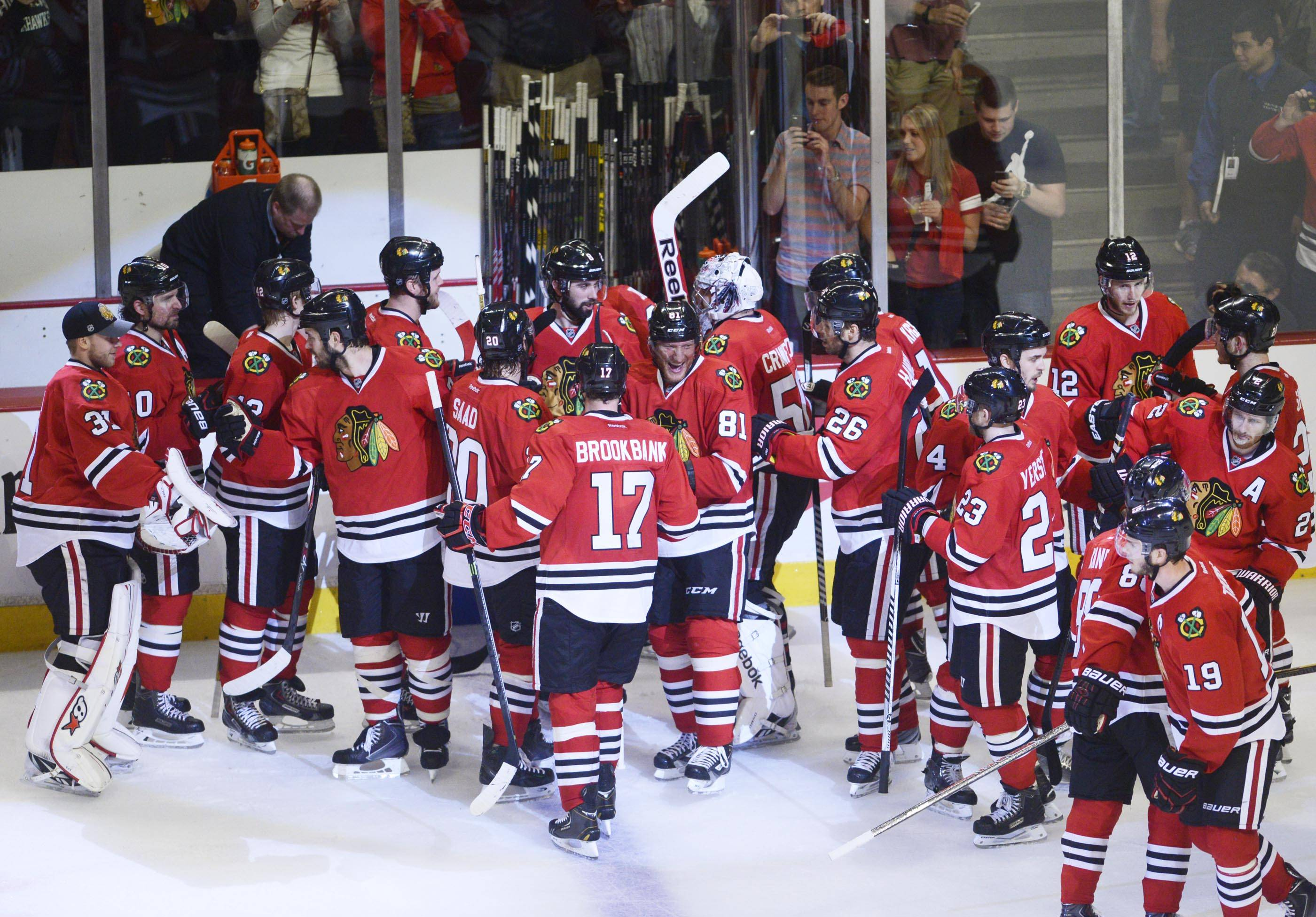 The Blackhawks gather Sunday around goalie Corey Crawford after their 2-1 win over the Minnesota Wild at United Center.