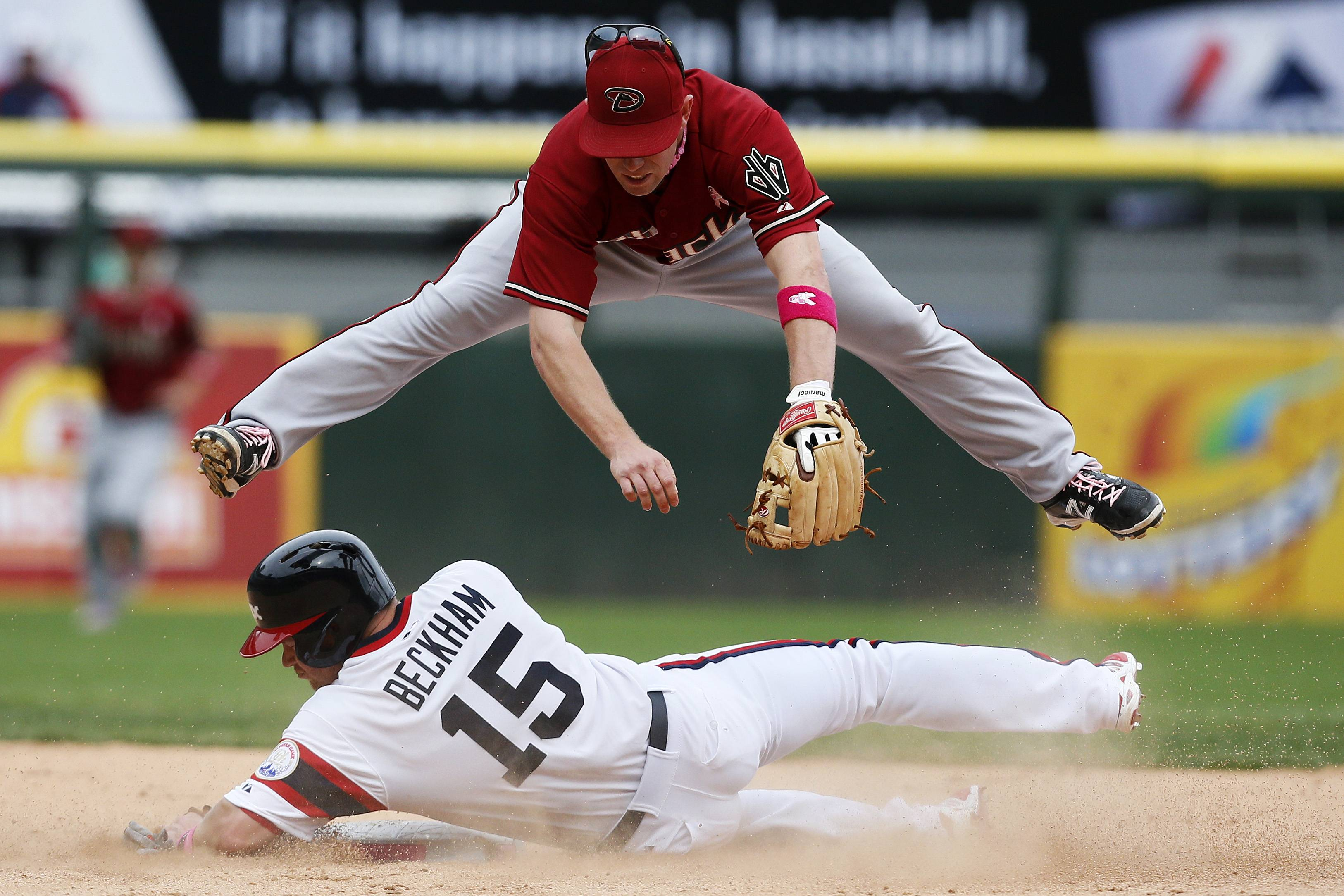 Arizona Diamondbacks second baseman Aaron Hill, top, forces out Chicago White Sox's Gordon Beckham on a double play to end the ninth inning of a baseball game on Sunday, May 11, 2014, in Chicago. The Diamondbacks won 5-1.