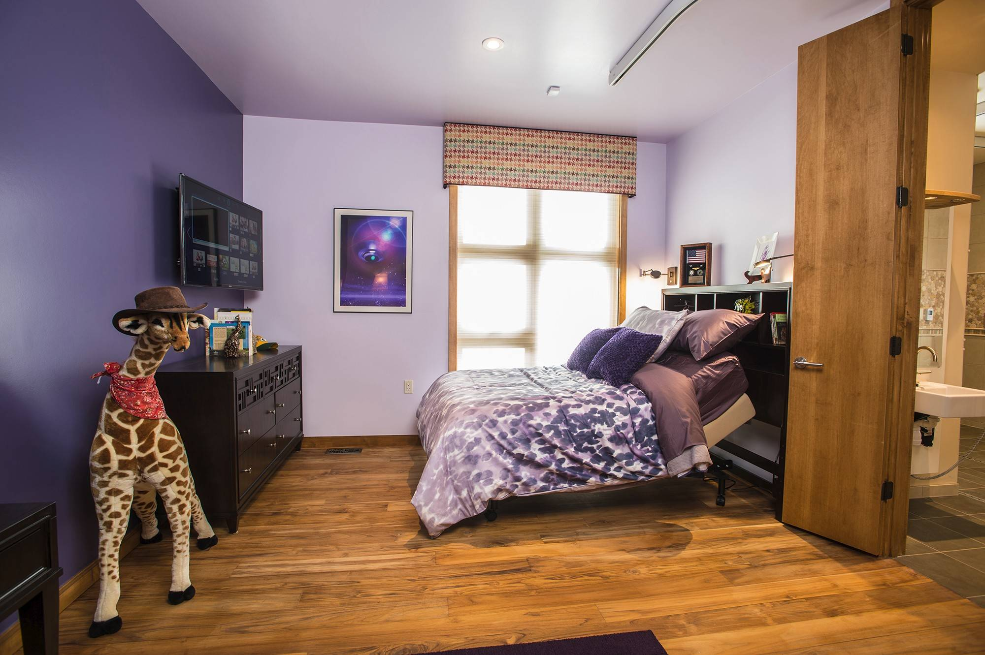 David's bedroom features a purple color scheme and a giraffe motif; the boys' bedrooms have a track system so they can move from bedroom to bath and vanity.