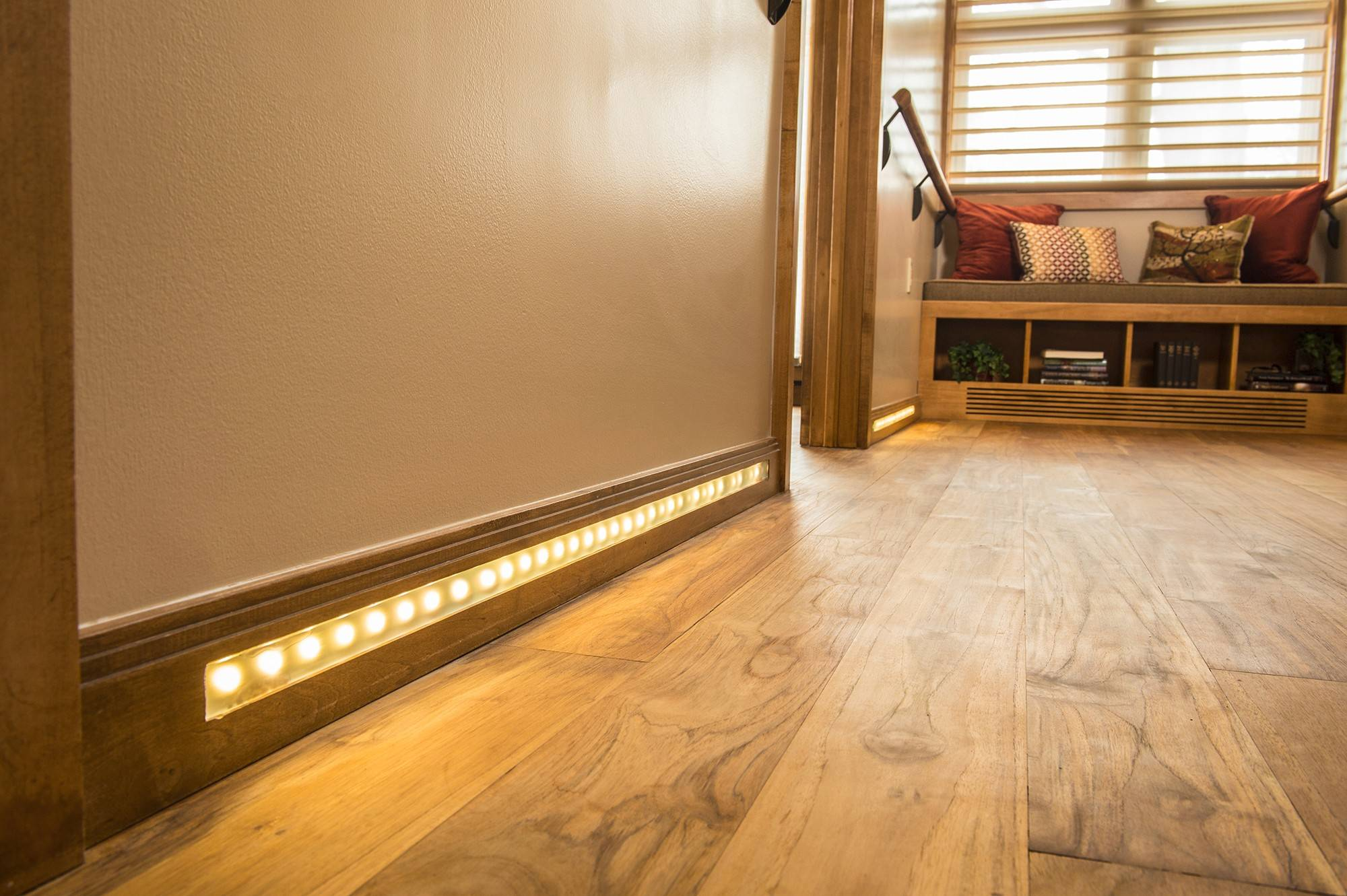 The hallway is illuminated 24 hours a day by low-voltage LED lighting strips in the baseboards. Brazilian teak handrails reflect the teak flooring, blending in instead of announcing that disabled children live here.