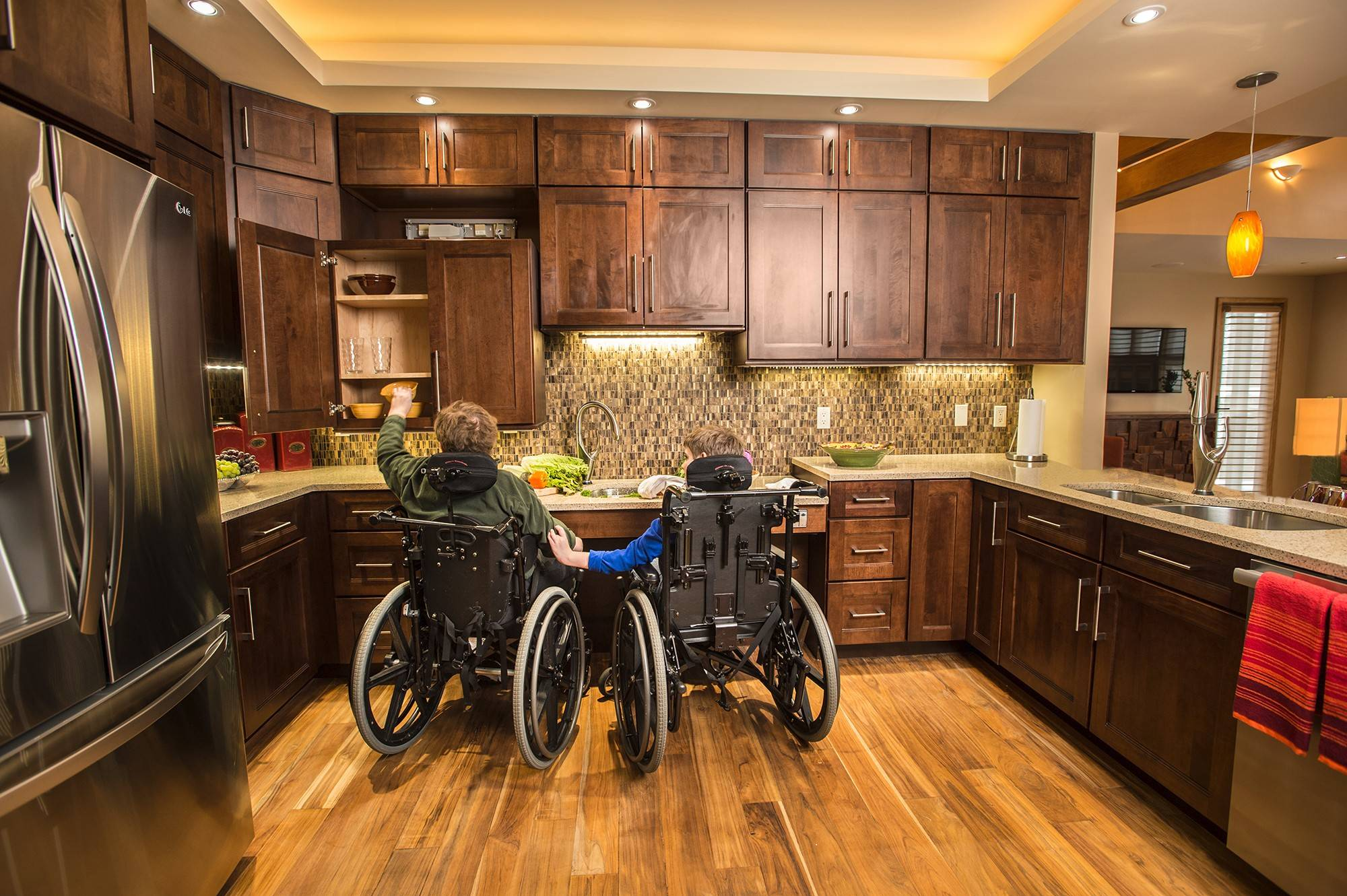 David and Joshua Cibula sit in the kitchen of their new home, which their parents built so the boys can live there with a caregiver after their parents are no longer able to care for them. In the kitchen, cabinetry and countertops can be lowered to provide access.