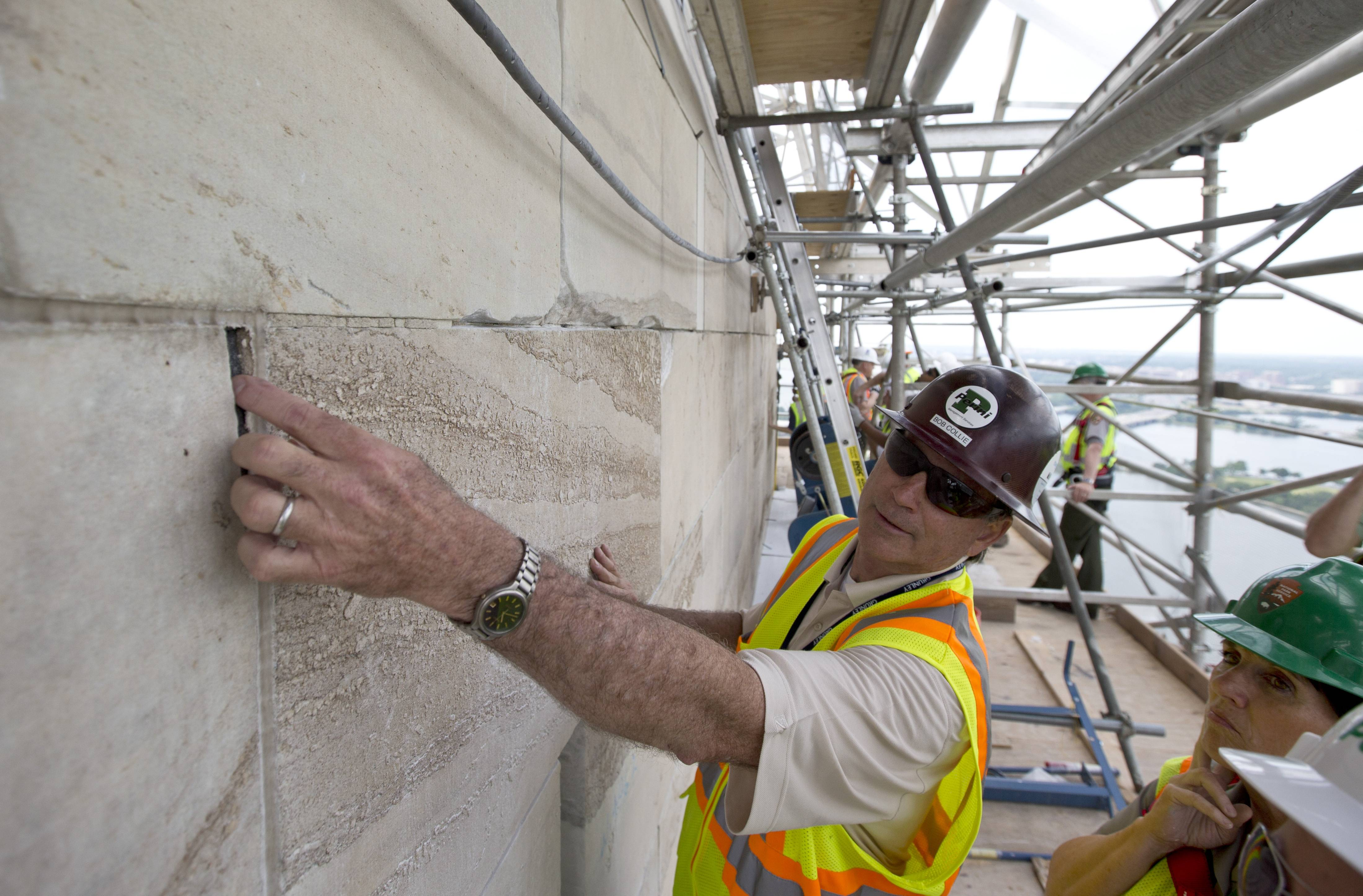 Bob Collie, project manager with Perini Management Services, puts his finger in a crack of the Washington Monument at the 491-foot level of the scaffolding surrounding the monument, in Washington, in this June 2, 2013, file photo.