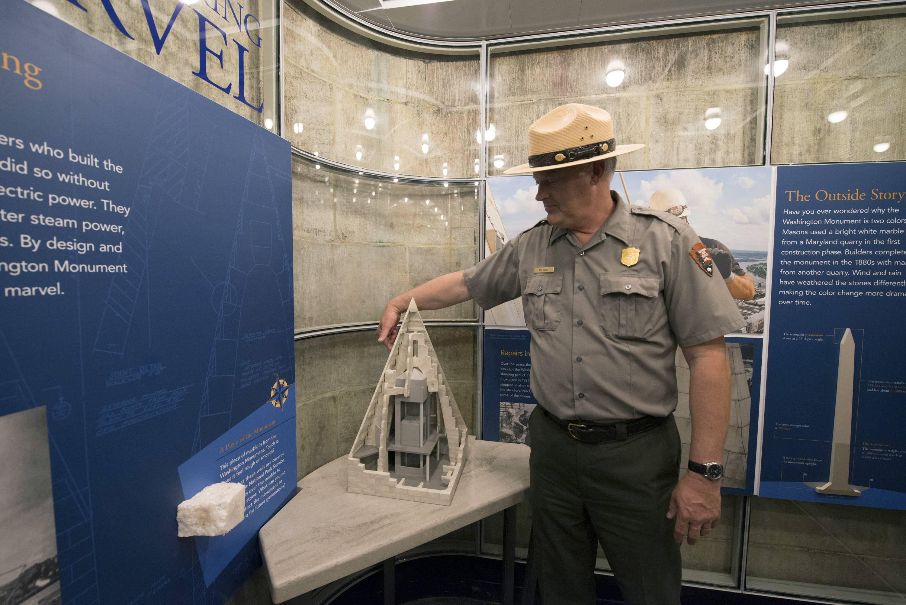 Bob Vogel, superintendent of National Mall and Memorial Parks, points out the location of a repaired crack on a scale model in a new exhibit inside the Washington Monument during a press preview Saturday prior to the re-opening of the monument.