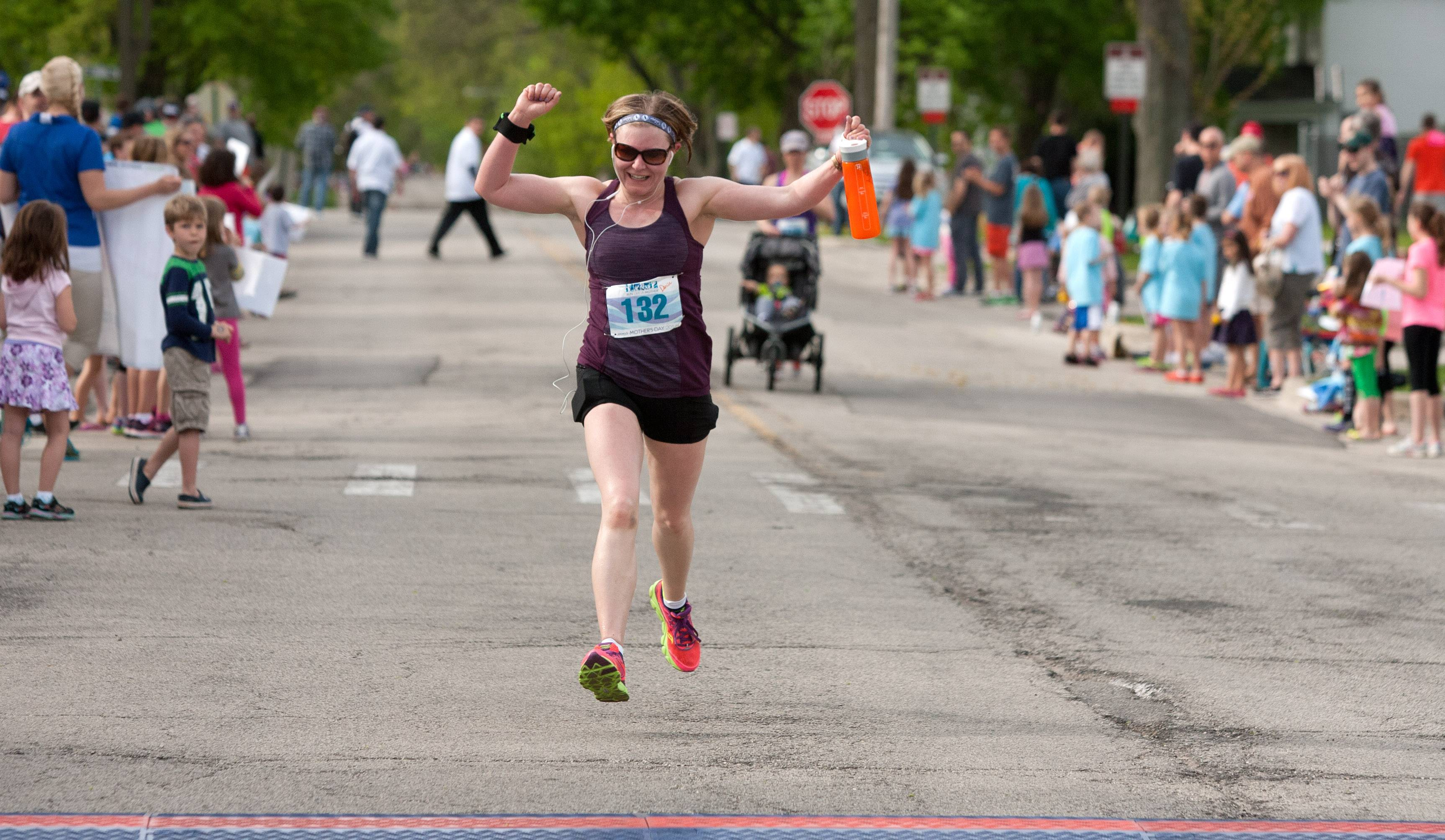 Denise Parejko of Clarendon Hills crosses the finish line during Sunday's Run Like a Mother 5K race in Hinsdale. The women-only run raises money to enrich the lives of children with Angelman syndrome.