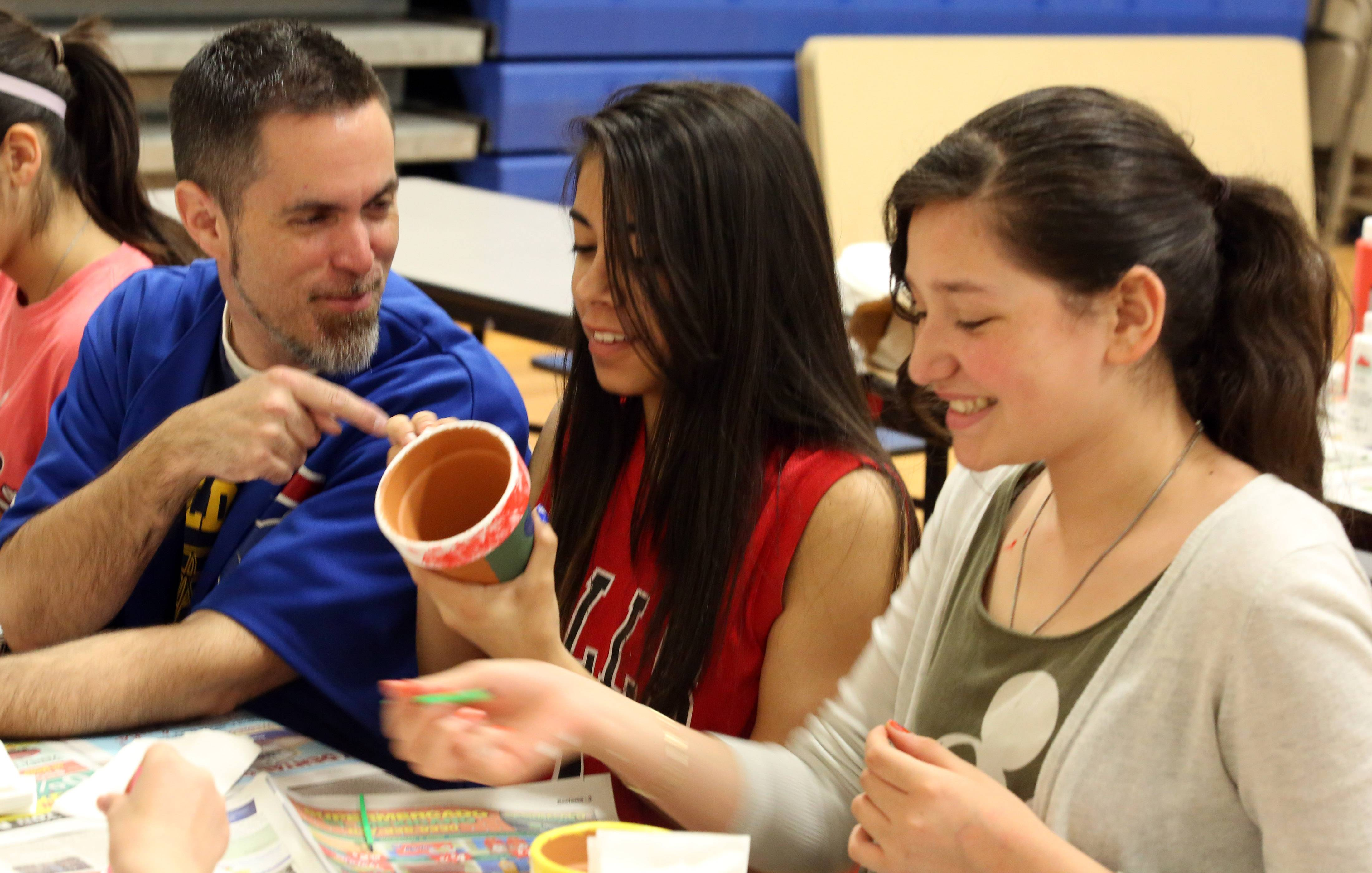 Jeff Prickett, principal at Round Lake Middle School, has a laugh with Alexcia Galvan, eighth grader, center, and Paola Morales, seventh grader, as they paint pots for Mother's Day gifts during the Second Saturday program at the school.