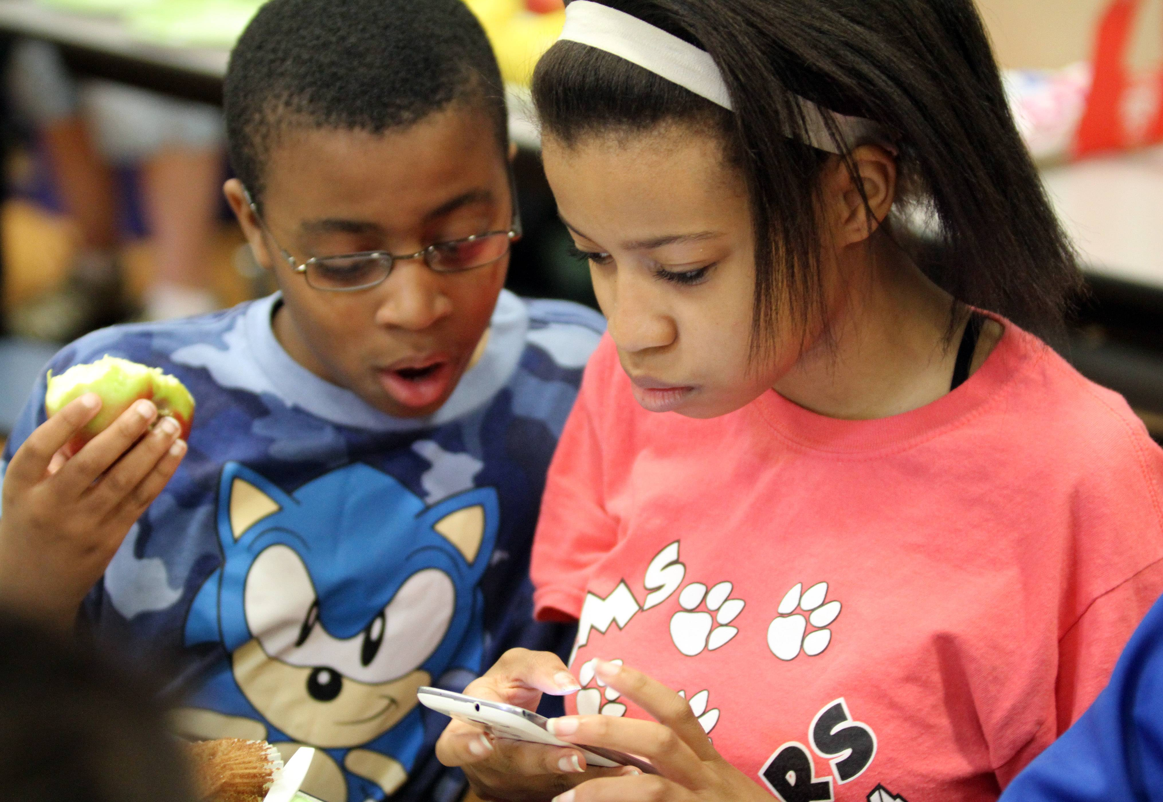Jordin Williams, eighth grader, shows her younger brother, Kenneth, a photo she took of him while they eat breakfast during the Second Saturday program at the school.
