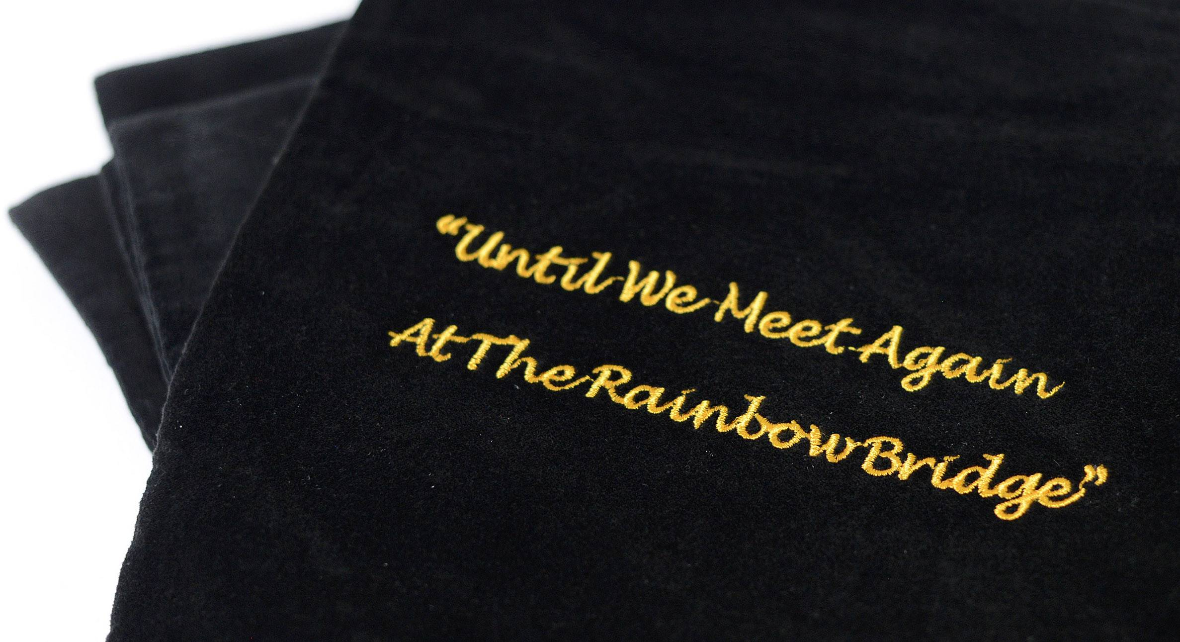 "The metal box with pet ashes is placed into velvet pouches inscribed with the ""Rainbow Bridge"" phrase."