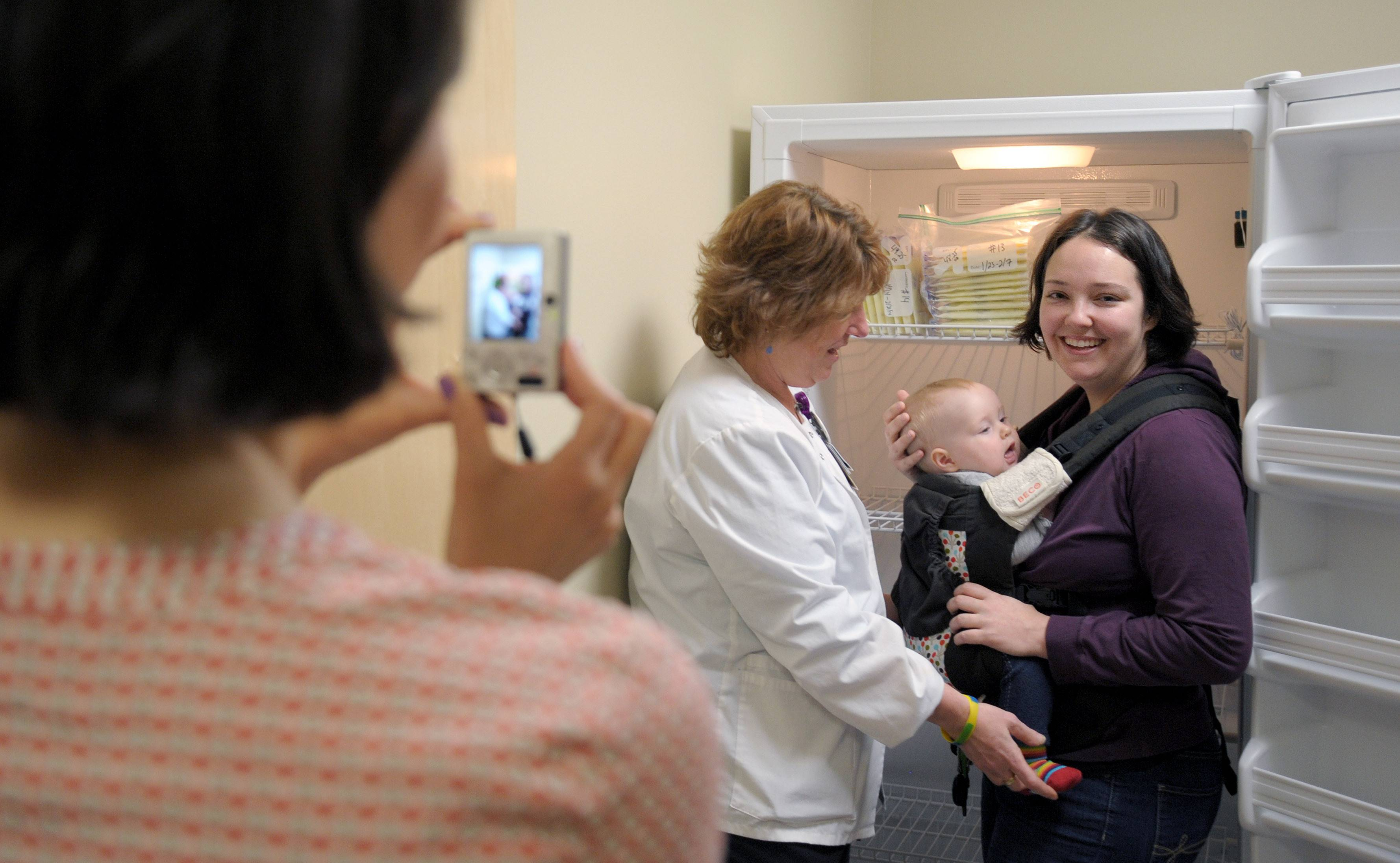 Holding her 8-month-old daughter, Lillian, Susan Urbanski of Niles drops off the first deposit of breast milk to nurse/lactation specialist Gina Juliano at the new breast milk depot at Advocate Sherman Hospital in Elgin. Jen Anderson, executive director of Mothers' Milk Bank of the Western Great Lakes, takes a photograph.