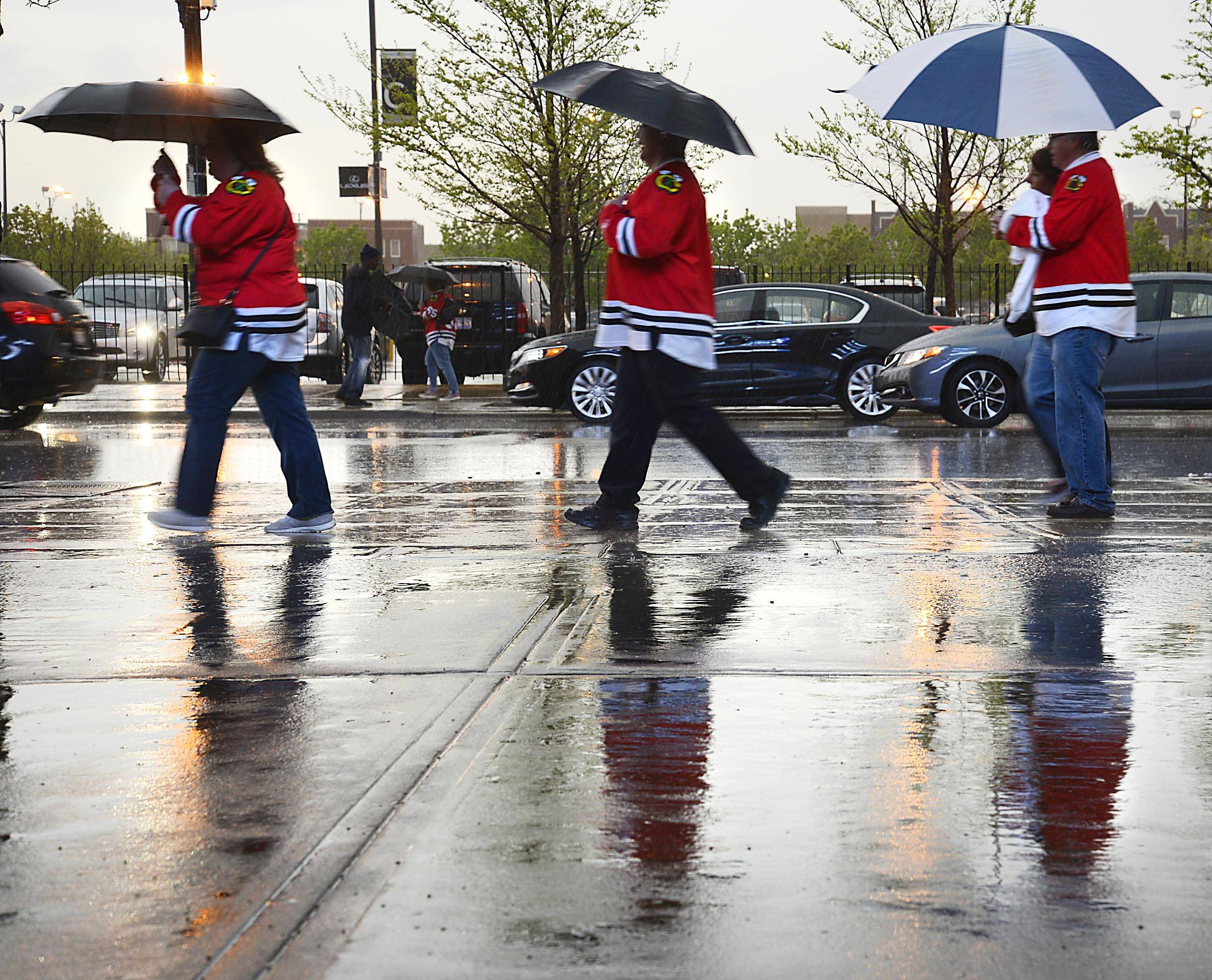 Blackhawks fans use umbrellas as they arrive in the rain Sunday at the United Center in Chicago for Game 5 of round 2 of the Stanley Cup Playoffs against the Minnesota Wild.