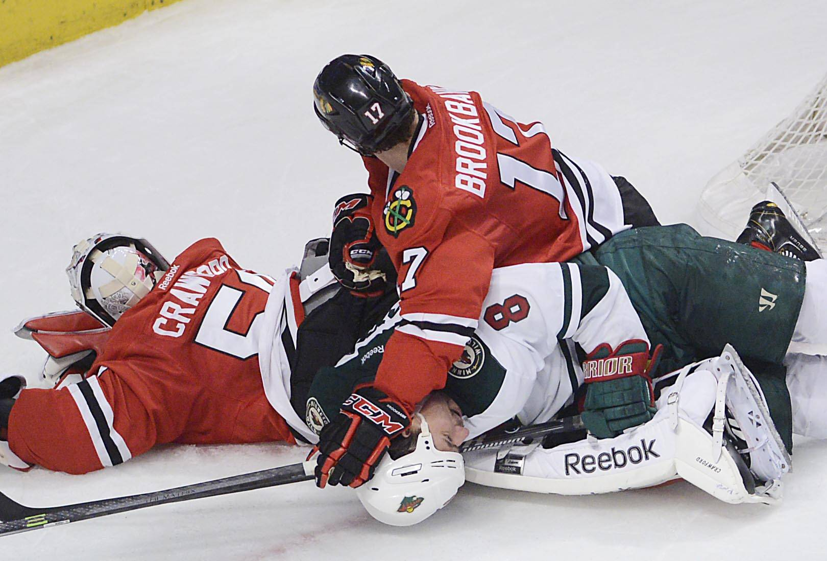Chicago Blackhawks defenseman Sheldon Brookbank pushes Minnesota Wild center Cody McCormick to the ice on top of goalie Corey Crawford in the second period.