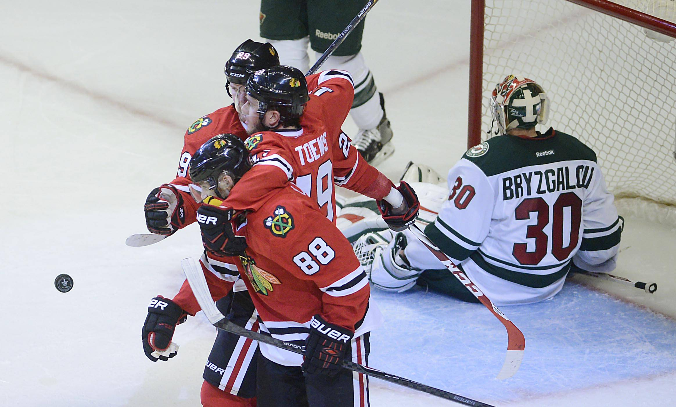 \Chicago Blackhawks forward Bryan Bickell is flanked by teammates Jonathan Toews and Patrick Kane after his second period goal against Minnesota Wild goalie Ilya Bryzgalov in the second period.