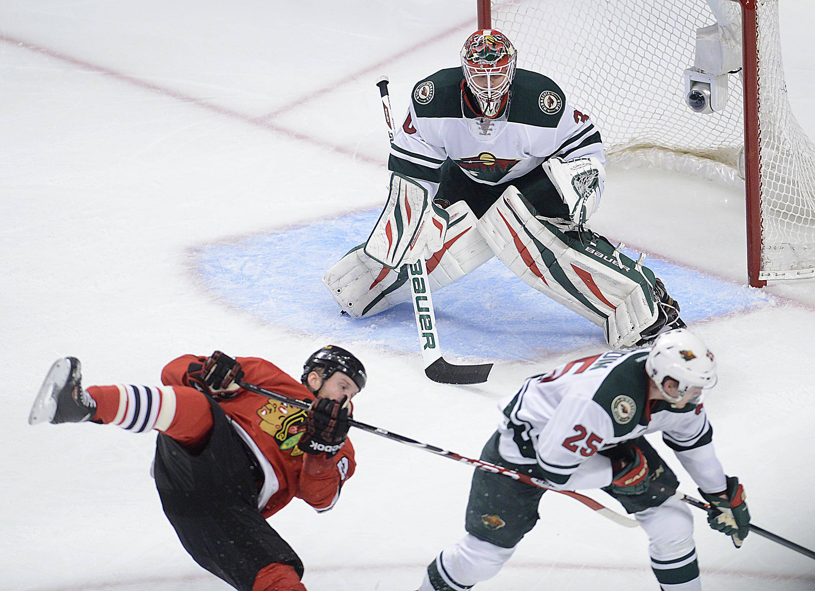 Chicago Blackhawks left wing Bryan Bickell is knocked off his skates by Minnesota Wild defenseman Jonas Brodin.