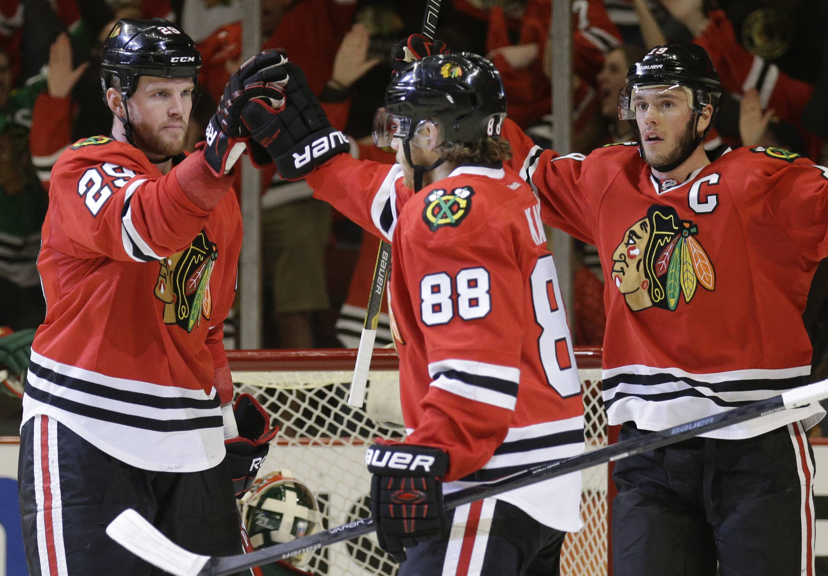 Chicago Blackhawks' Bryan Bickell (29), left, celebrates with Patrick Kane (88) and Jonathan Toews (19) after scoring his goal against the Minnesota Wild during the second period.