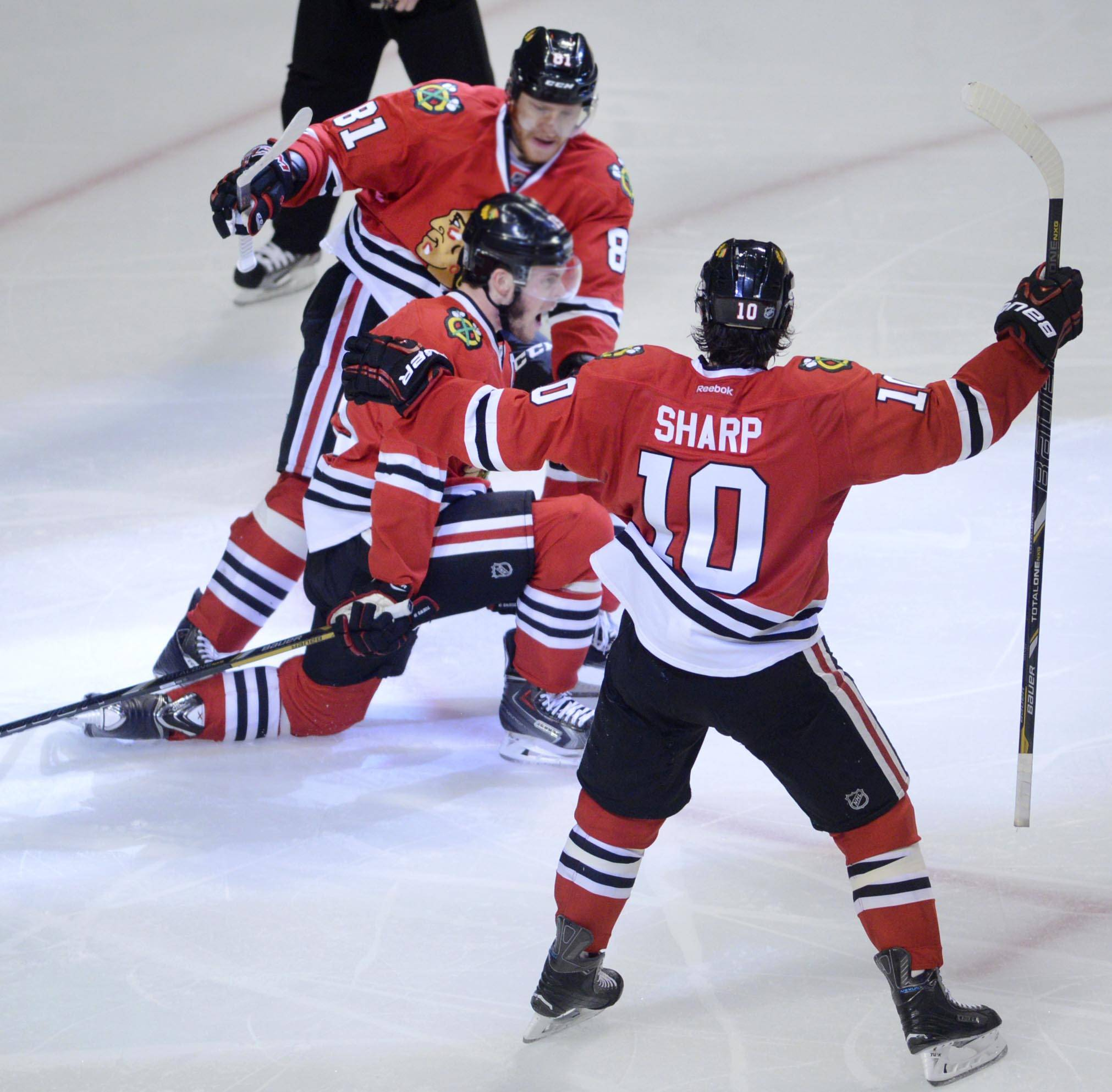 Chicago Blackhawks center Jonathan Toews celebrates his game-winning goal of the game in the third period with teammates Marian Hossa and Patrick Sharp.