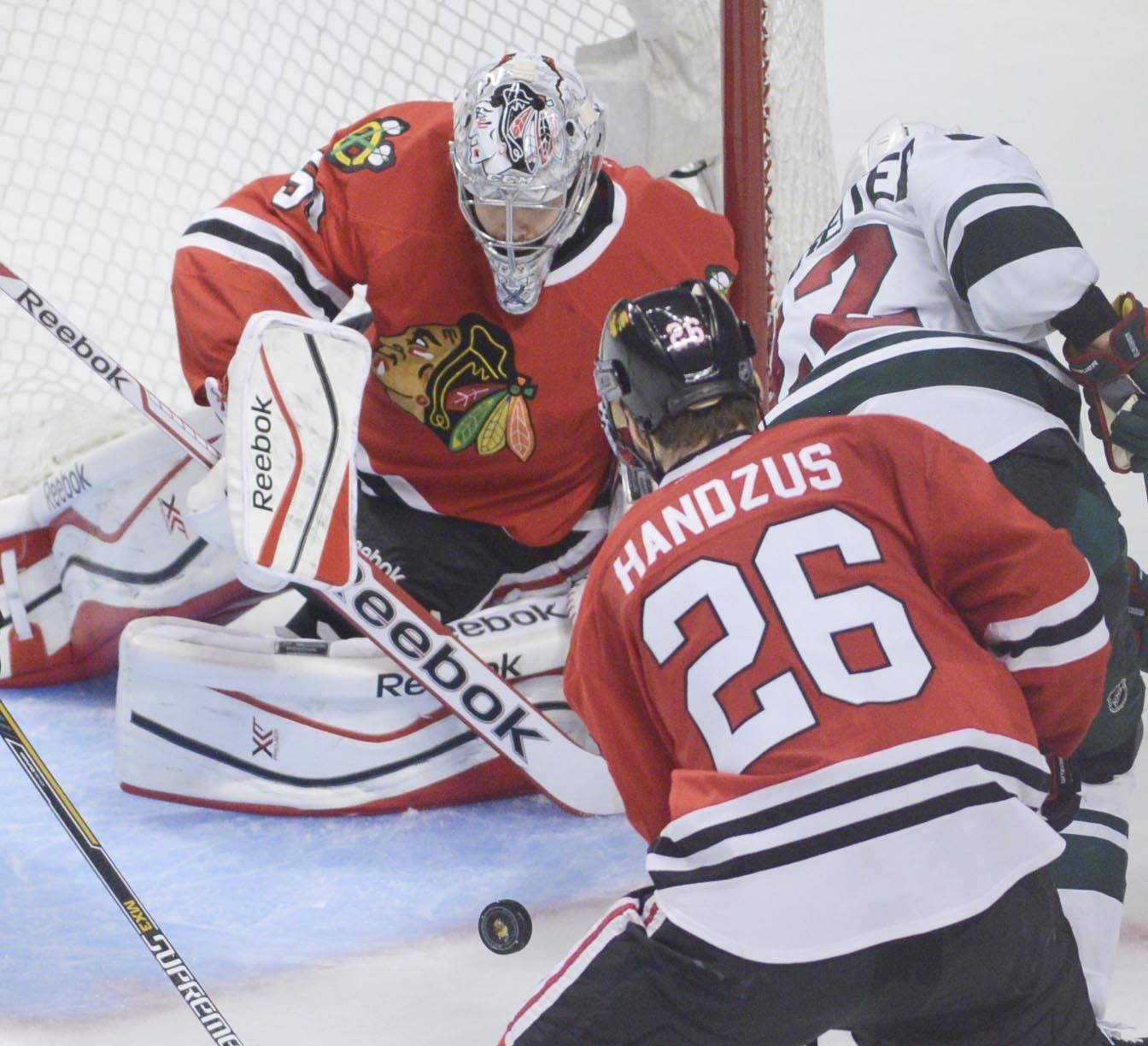 Chicago Blackhawks goalie Corey Crawford makes one of his 27 saves against the Minnesota Wild Sunday in Game 5.
