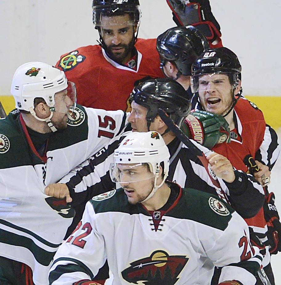 Chicago Blackhawks right wing Ben Smith screams at Minnesota Wild left wing Dany Heatley and right wing Nino Niederreiter as time expires in the Hawks 2-1 win Sunday in Game 5.