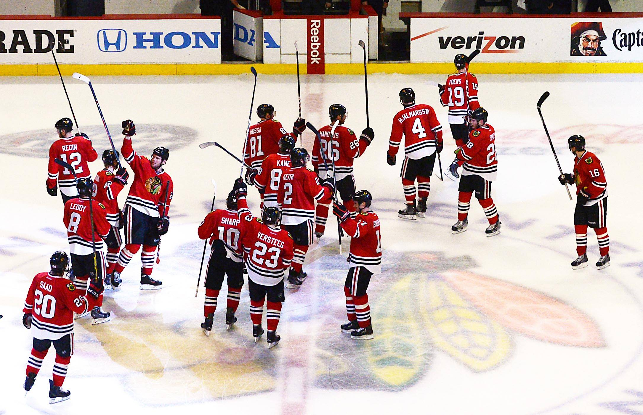 The Chicago Blackhawks raise their sticks after their 2-1 win over the Minnesota Wild Sunday.