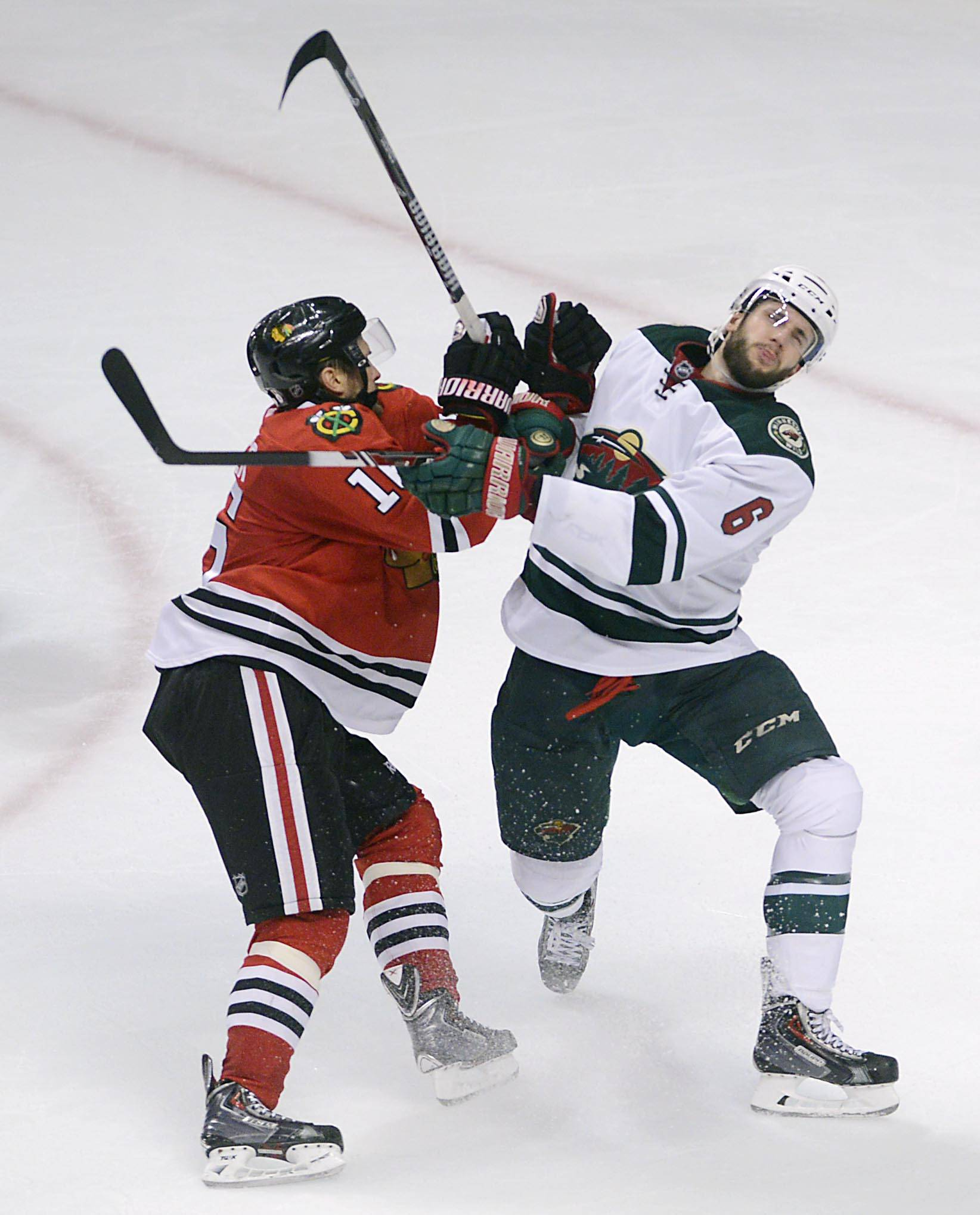 Chicago Blackhawks center Marcus Kruger hits Minnesota Wild defenseman Marco Scandella.