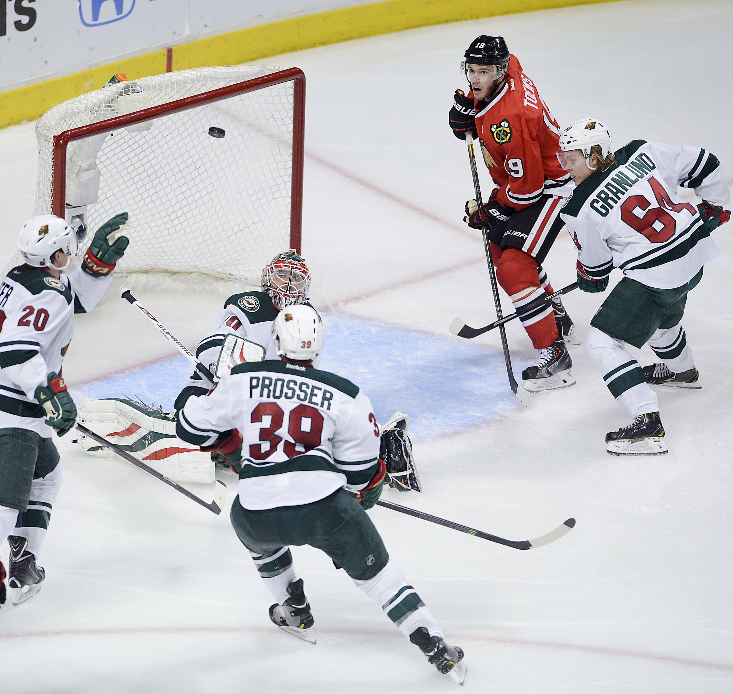 Chicago Blackhawks center Jonathan Toews and Minnesota Wild's Ryan Suter, Nate Prosser, Mikael Granlund and goalie Ilya Bryzgalov watch the puck bounce high in front of the net. Toews eventually scored on the play.