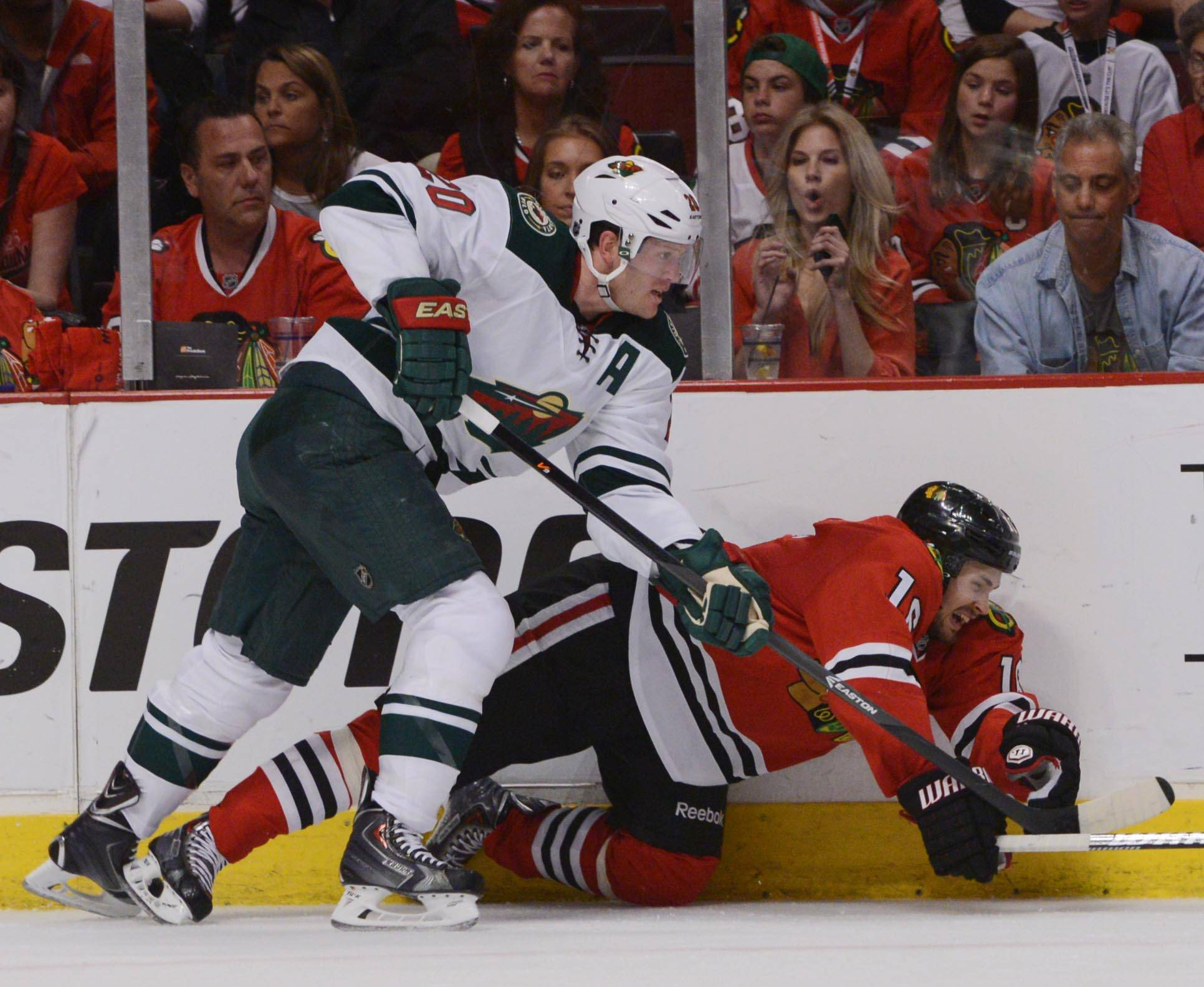 Chicago Blackhawks center Marcus Kruger gets knocked to the ice by Minnesota Wild defenseman Ryan Suter.
