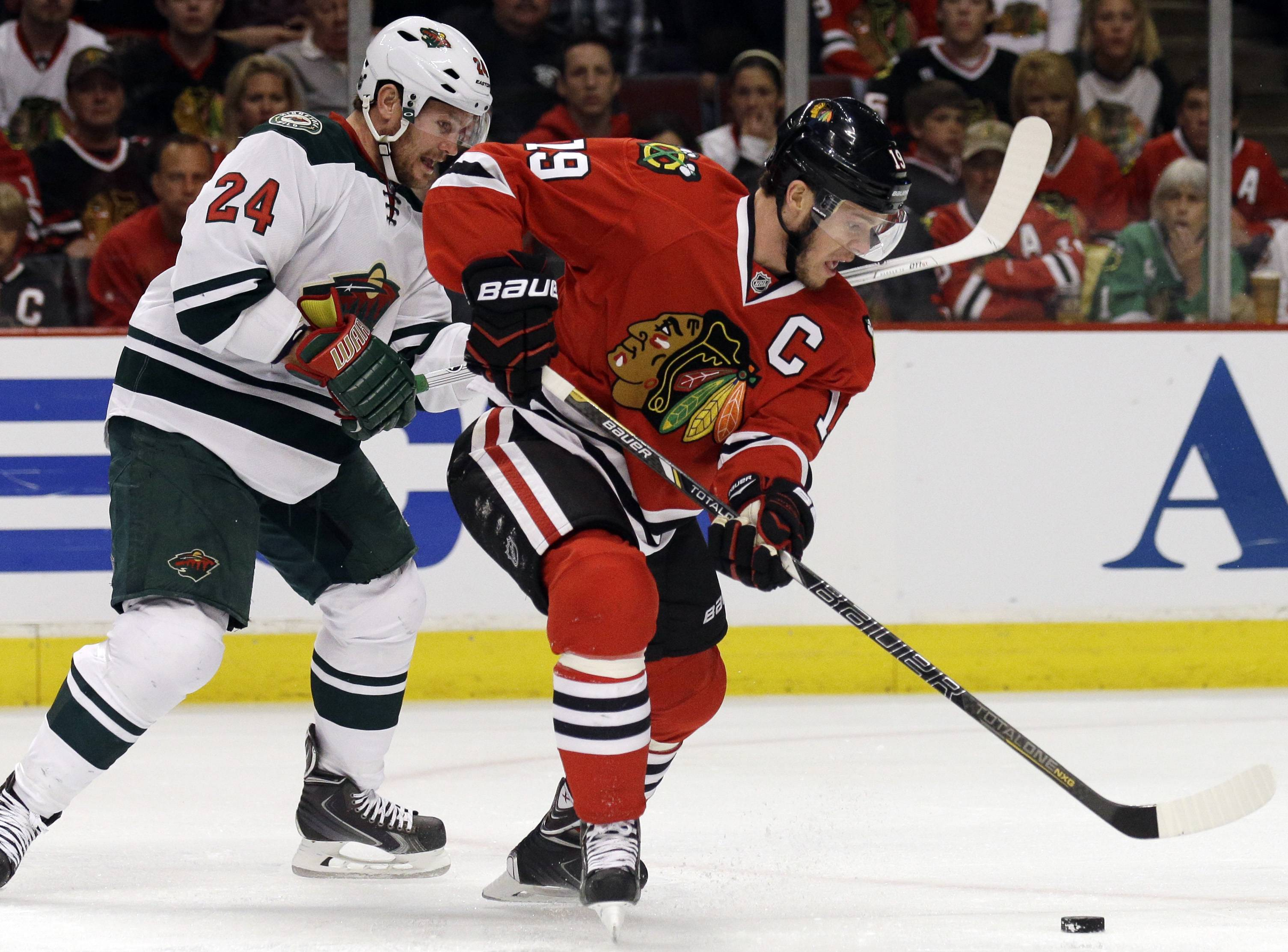 Chicago Blackhawks' Jonathan Toews (19), right, controls the puck against Minnesota Wild's Matt Cooke (24) during the first period.