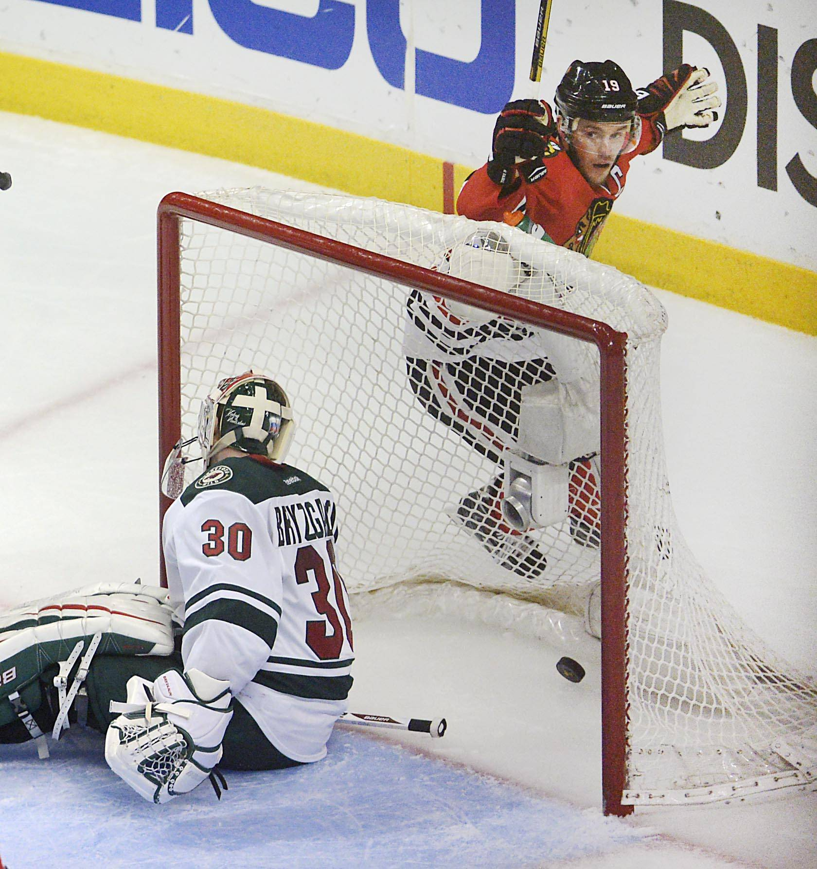 Chicago Blackhawks center Jonathan Toews celebrates after Bryan Bickell's second period goal as he circles the net behind Minnesota Wild goalie Ilya Bryzgalov.