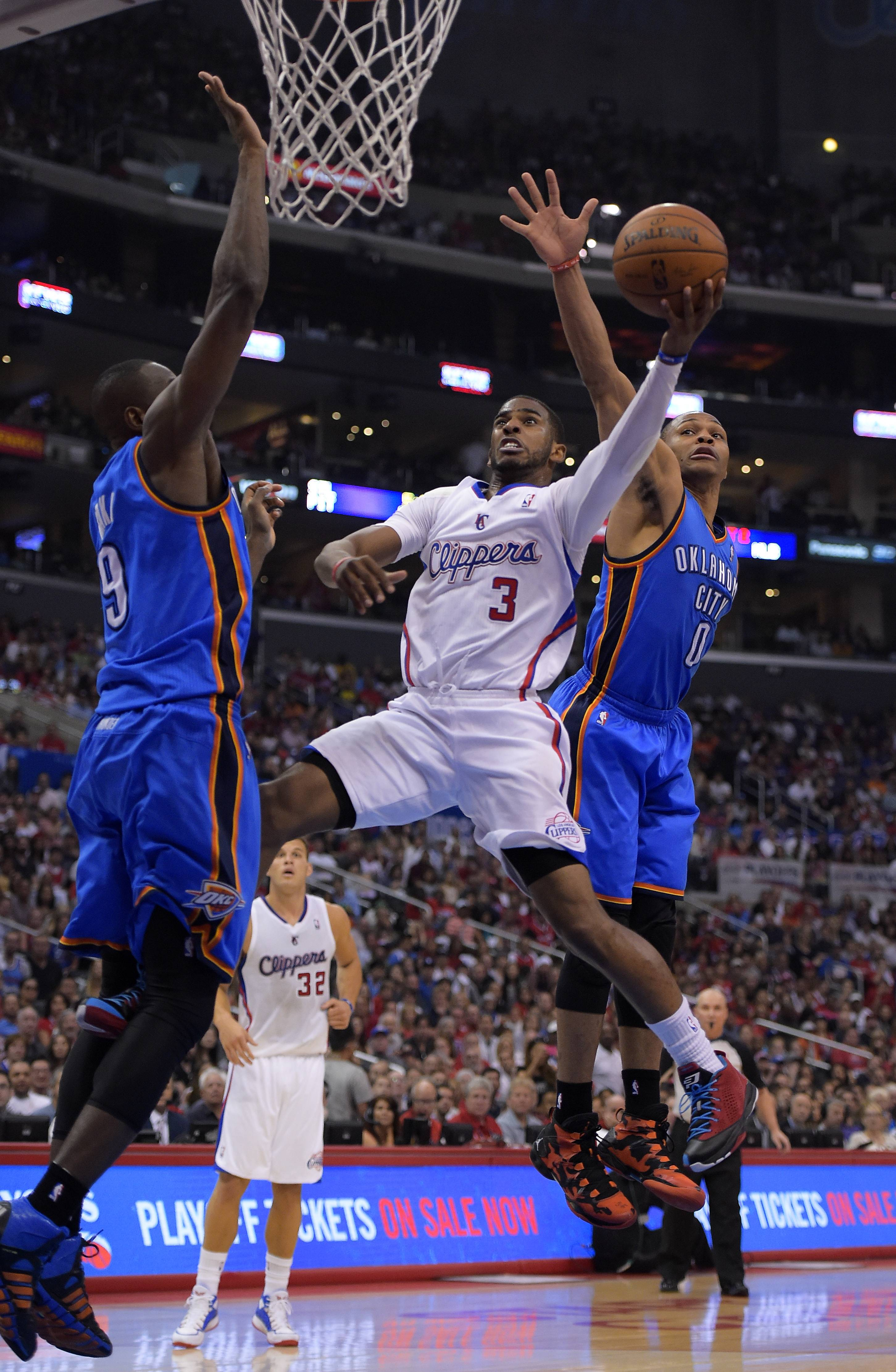 Los Angeles Clippers guard Chris Paul, center, puts up a shot between Oklahoma City Thunder defenders Serge Ibaka, left, of Congo, and Russell Westbrook in the first half of Game 4 of the Western Conference semifinal NBA basketball playoff series, Sunday, May 11, 2014, in Los Angeles.