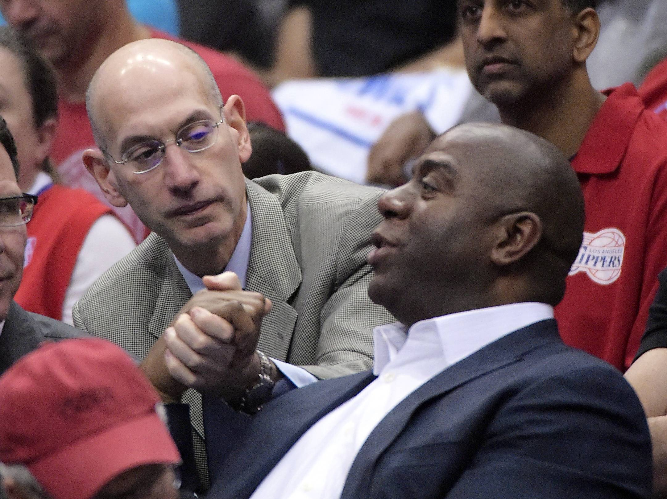 NBA Commissioner Adam Silver, left, shakes hands with Magic Johnson as they watch the Los Angeles Clippers play the Oklahoma City Thunder in the first half of Game 4 of the Western Conference semifinal NBA basketball playoff series, Sunday, May 11, 2014, in Los Angeles.