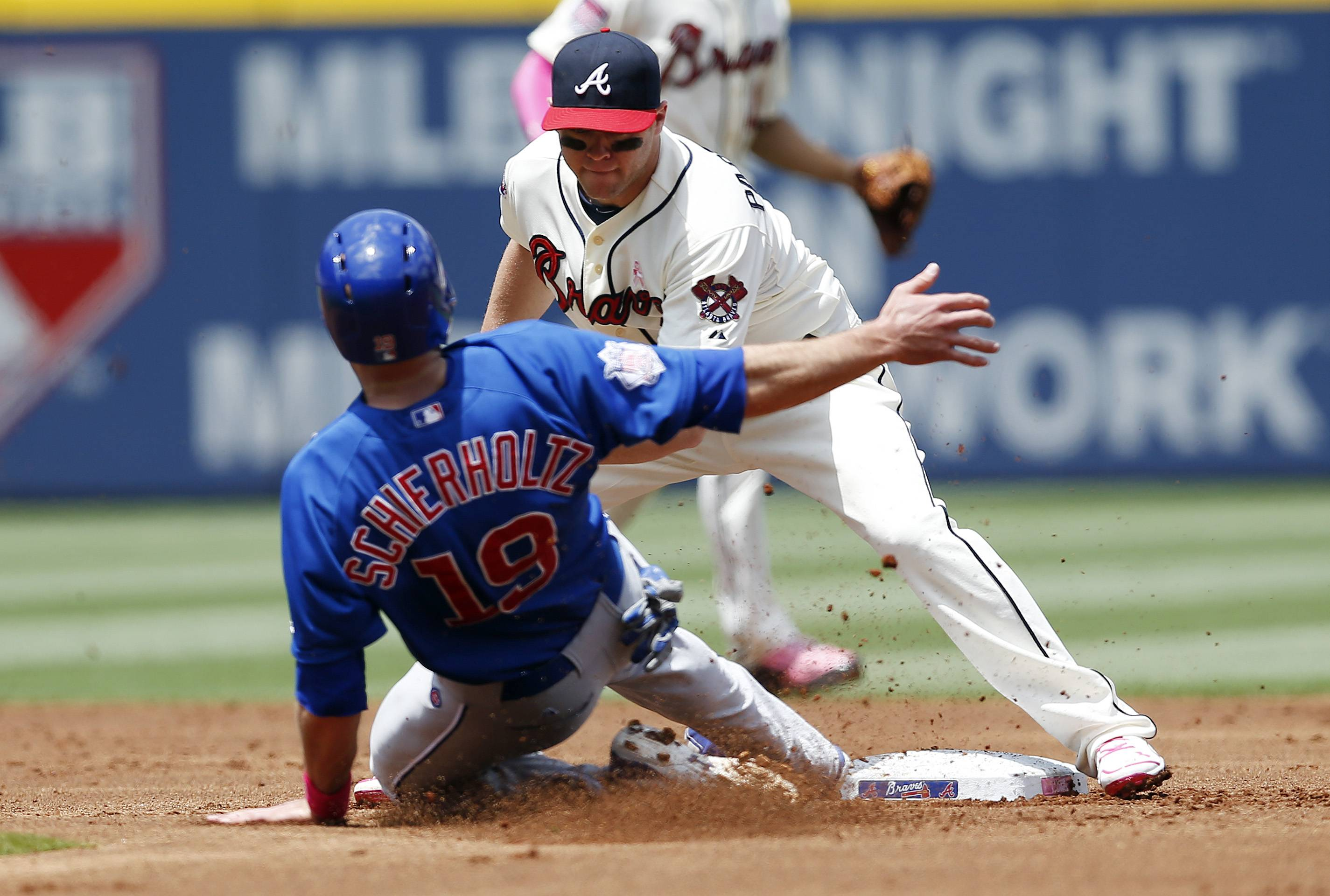 The Cubs' Nate Schierholtz (19) is tagged out by Atlanta Braves second baseman Tyler Pastornicky while trying to steal second base in the second inning of a baseball game on Sunday, May 11, 2014, in Atlanta.