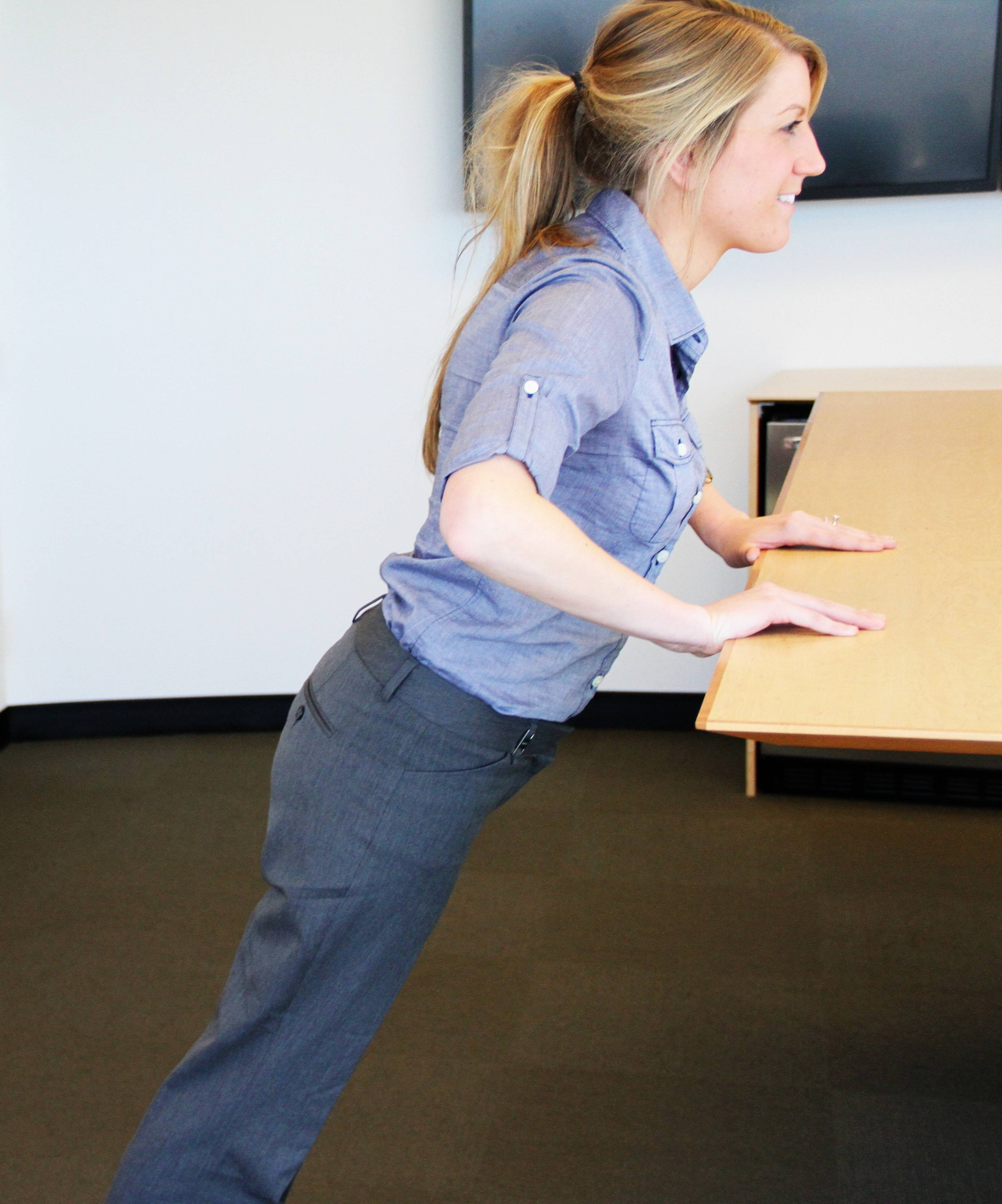 Jill Micklow, Wellness Specialist at Assurance, demonstrates that modified push-ups can be done anywhere in the office.
