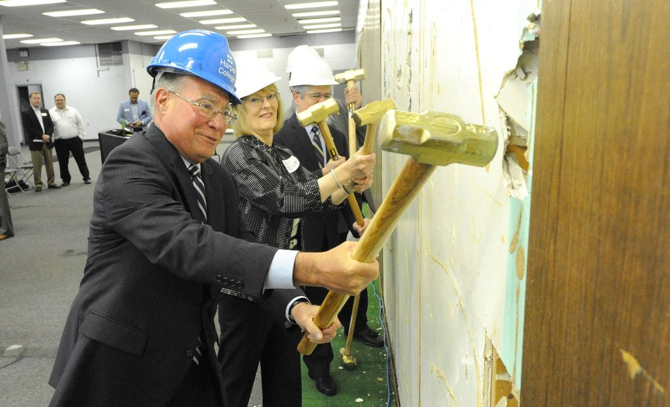 Harper College President Ken Ender and Harper Board Chair Diane Hill are among those swinging sledgehammers into a wall to start construction Monday of the Hanover Park Education and Work Center.