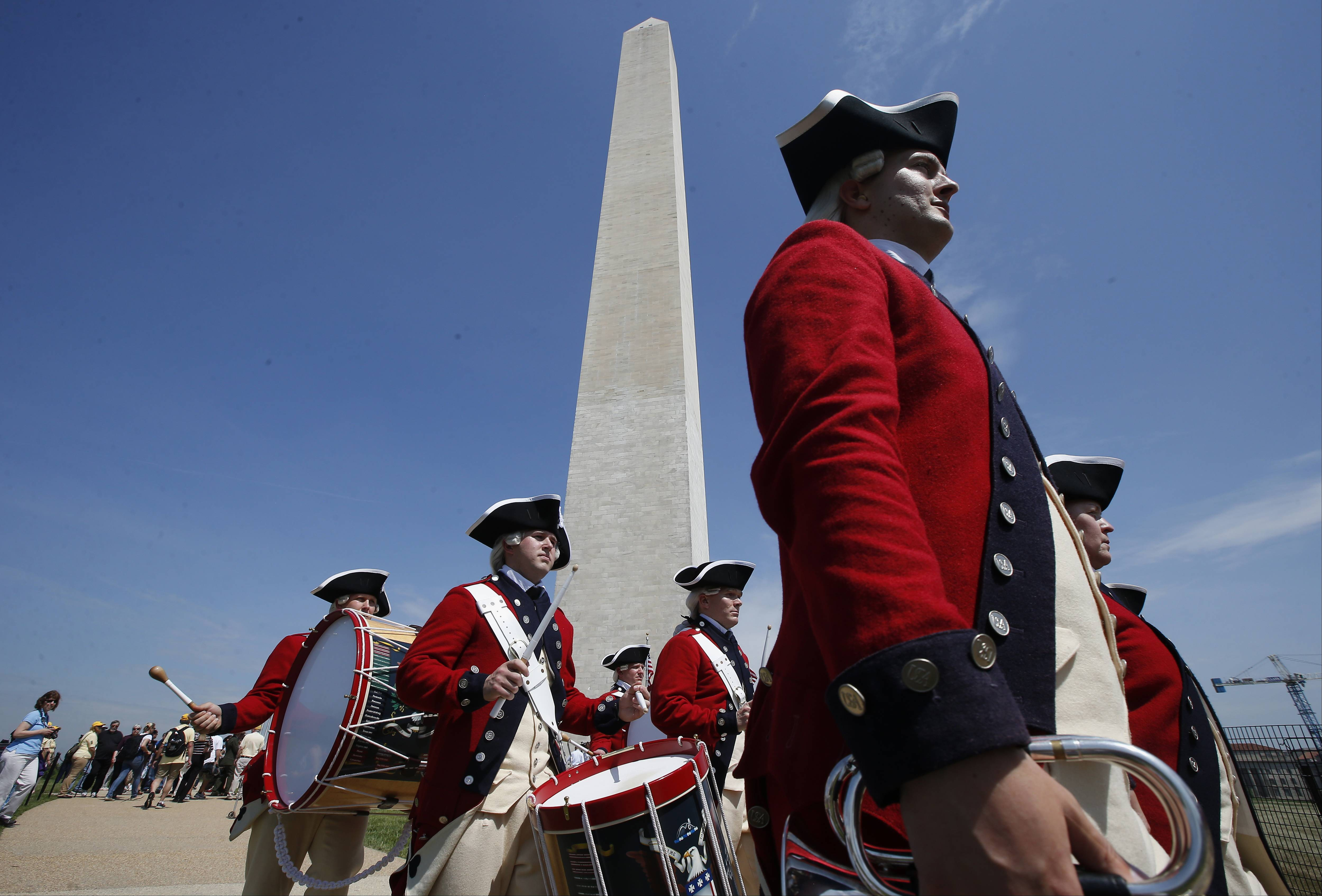 Members of the United States Army Old Guard Fife and Drums Corps march beneath the Washington Monument on Monday during a ceremony to celebrate its reopening.